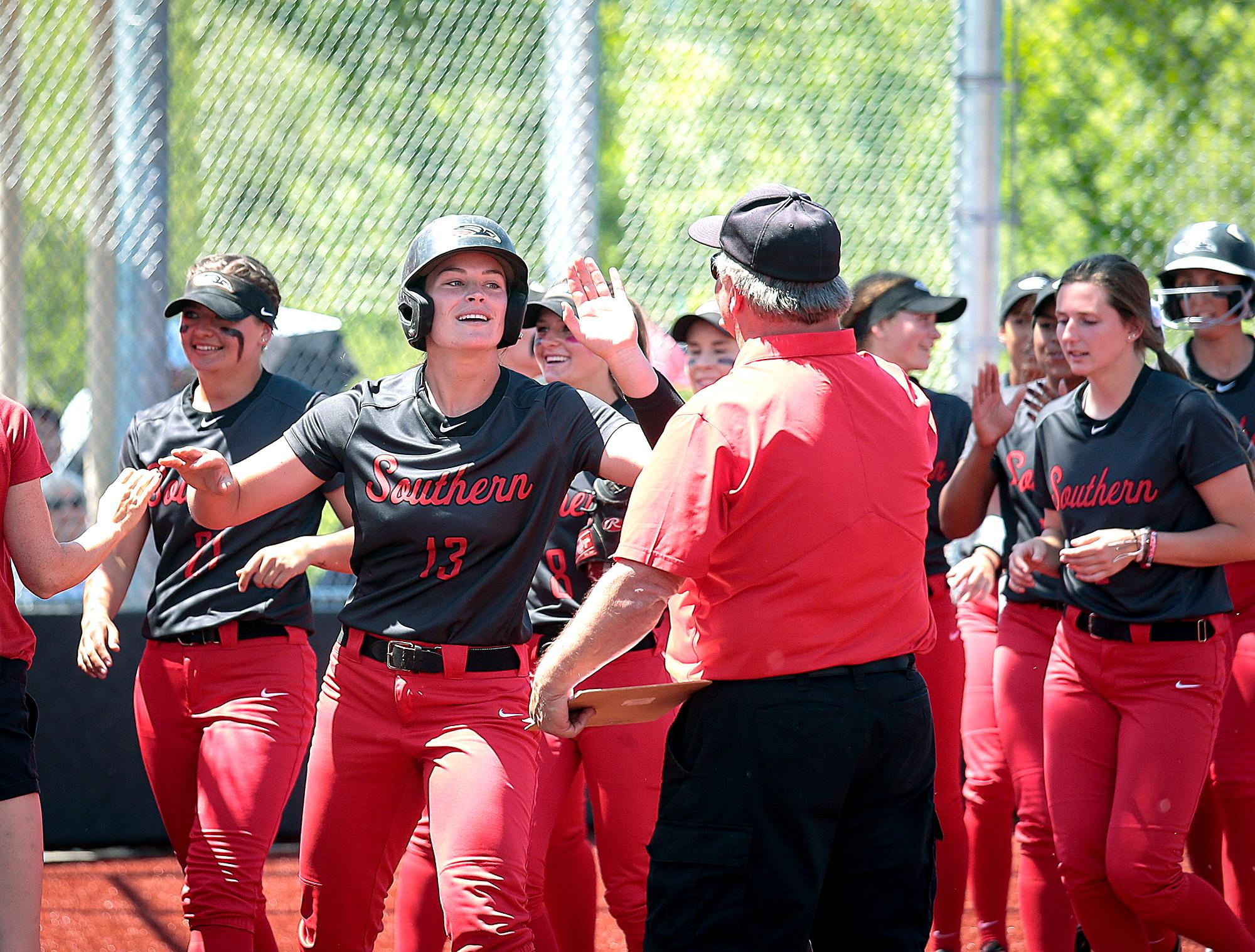 Southern Oregon University's Harlee Donovan (13) celebrates with teammates and coaches after hitting a 2-run blast in the First Inning against Simpson at US Cellular Fields on Monday.  [PHOTO BY:  LARRY STAUTH JR]