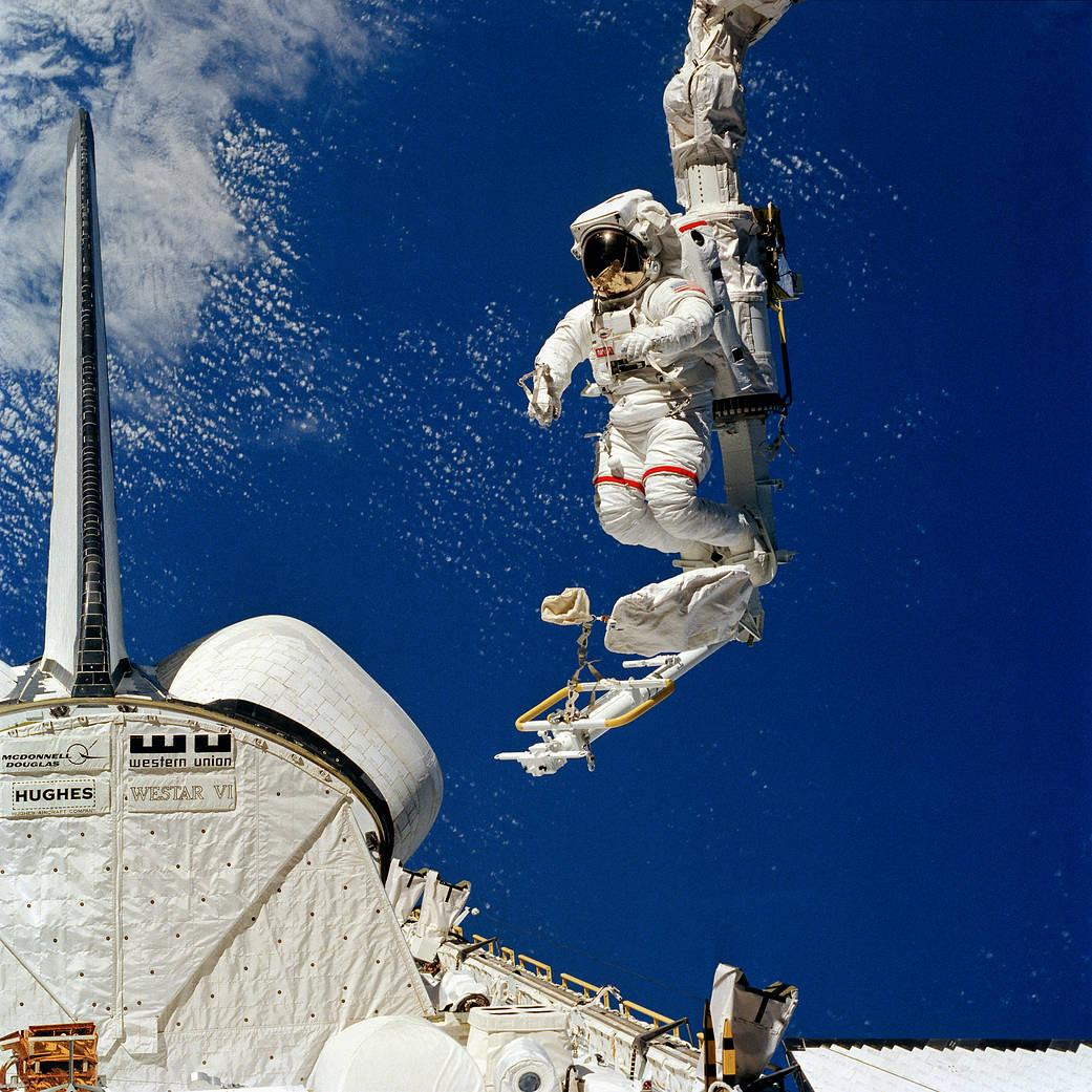 <p>Astronaut Bruce McCandless II, pictured leaning out into space as his feet are anchored in the mobile foot restraint (MFR), and moved around by the remote manipulator system (RMS). The aft portion of the space shuttle Challenger, to which the RMS is connected, is seen in lower left corner. This Feb. 7, 1984, photograph is one of a sequence showing McCandless in the device. On this same EVA, McCandless also initiated use of the manned maneuvering unit (MMU), not pictured here, a nitrogen-propelled back pack apparatus allowing for free movement in space. (Image Credit: NASA)</p>