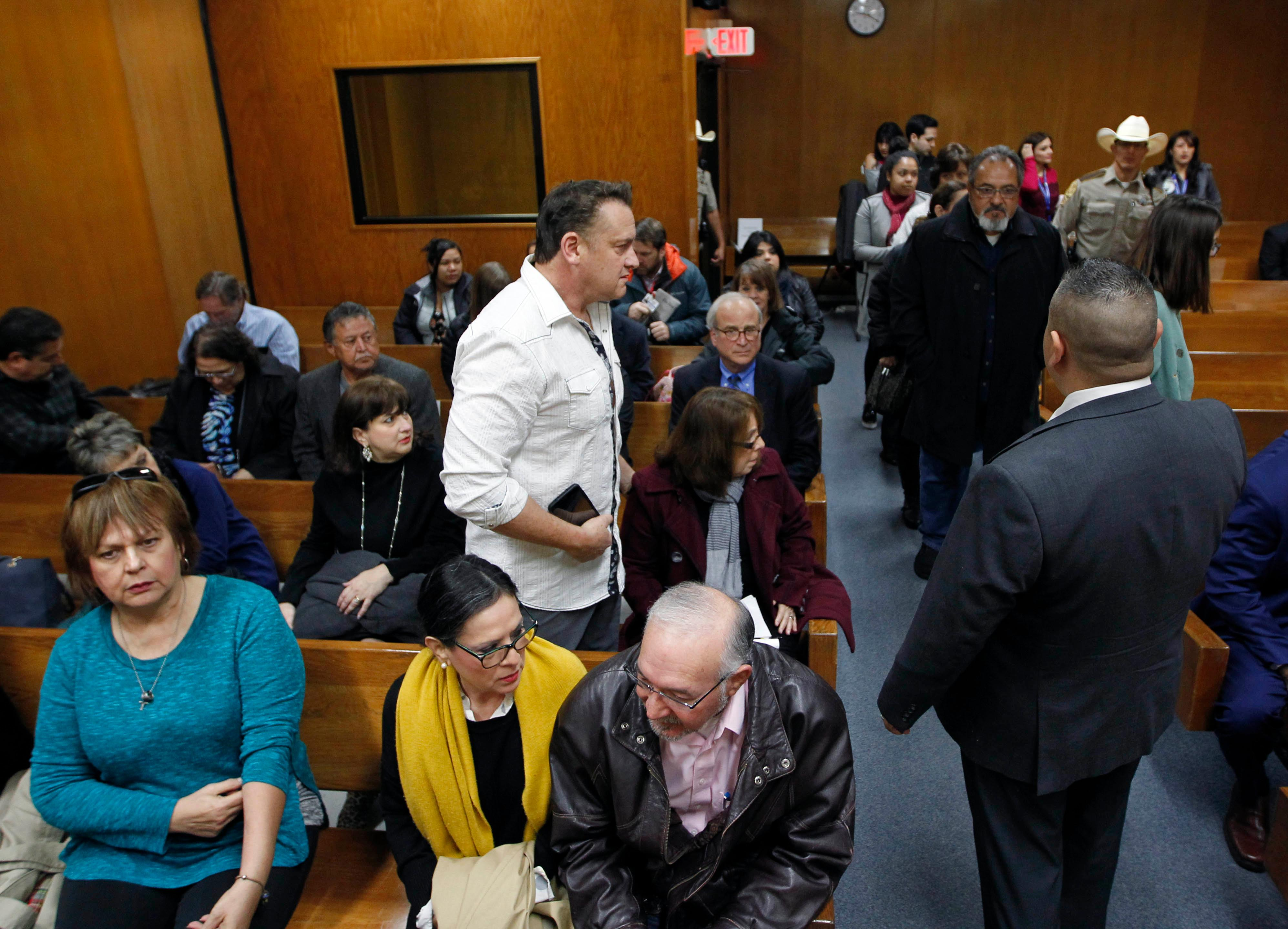 Nick Cavazos, standing, finds a seat in the 92nd state District Court with fellow family members of Irene Garza Lynda de la Vi?a, seated center, and Noemi Sigler, bottom left, before the start of closing arguments in John Bernard Feit's trial for the 1960 murder of Irene Garza in the 92nd state District Court Thursday, December 7, 2017, at the Hidalgo County Courthouse in Edinburg.  (Nathan Lambrecht/The Monitor/Pool)