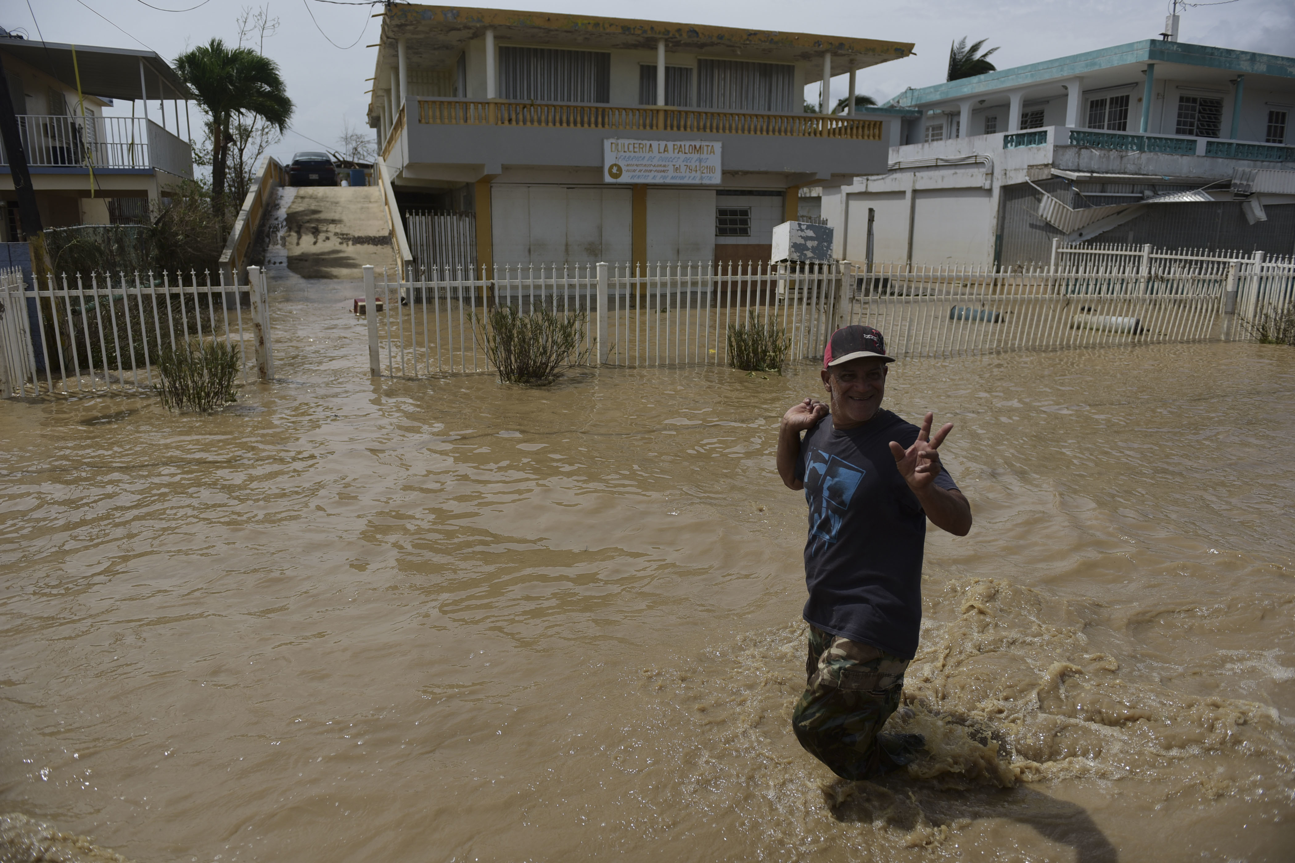 A resident wades through a flooded road in the Toa Ville community two days after the impact of Hurricane Maria in Toa Baja, Puerto Rico, Friday, Sept. 22, 2017. Because flooding, thousands of people are being evacuated from Toa Baja after the municipal government opened the gates of the Rio La Plata Dam. (AP Photo/Carlos Giusti)