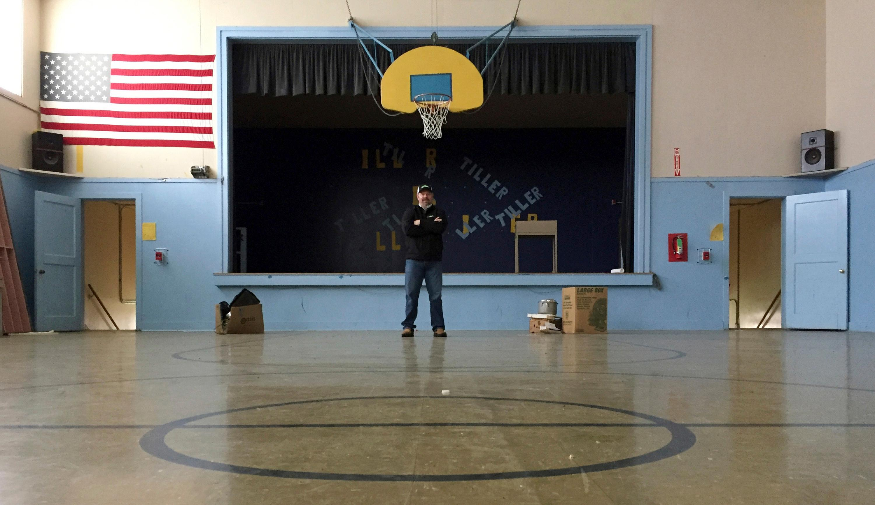 In this April 5, 2017 photo, Garrett Zoller, principal broker with LandandWildlife.com, stands under a basketball hoop in the abandoned gym of Tiller Elementary School in Tiller, Ore. Zoller is working to sell almost all of the downtown of the tiny, dying timber town for a total of $3.85 million. A potential buyer has come forward but is remaining anonymous -- and back-up offers are still being accepted. (AP Photo/Gillian Flaccus)