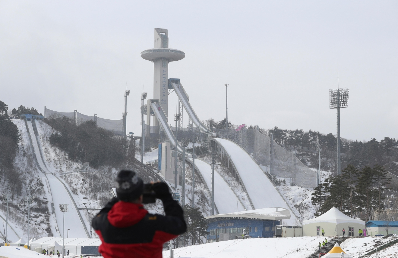 In this Sunday, Feb. 5, 2017 photo, a visitor takes a photo of the Alpensia Ski Jumping Center where is a venue for the 2018 Pyeongchang Winter Olympics in Pyeongchang, South Korea. One year before the Olympics, the country is in political disarray, and winter sports are the last thing on many people's minds. To say that South Koreans are distracted from what had been billed as a crowning sports achievement is an understatement. (AP Photo/Lee Jin-man)