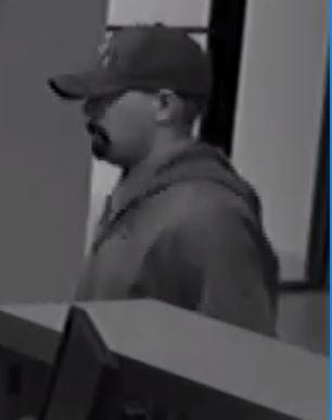 "The man is described white, 25-35 years old, 5'9"", 180 - 200 lbs., wearing a gray hooded sweatshirt over a dress shirt and tie, khaki pants, baseball cap with white lettering and fake facial hair."