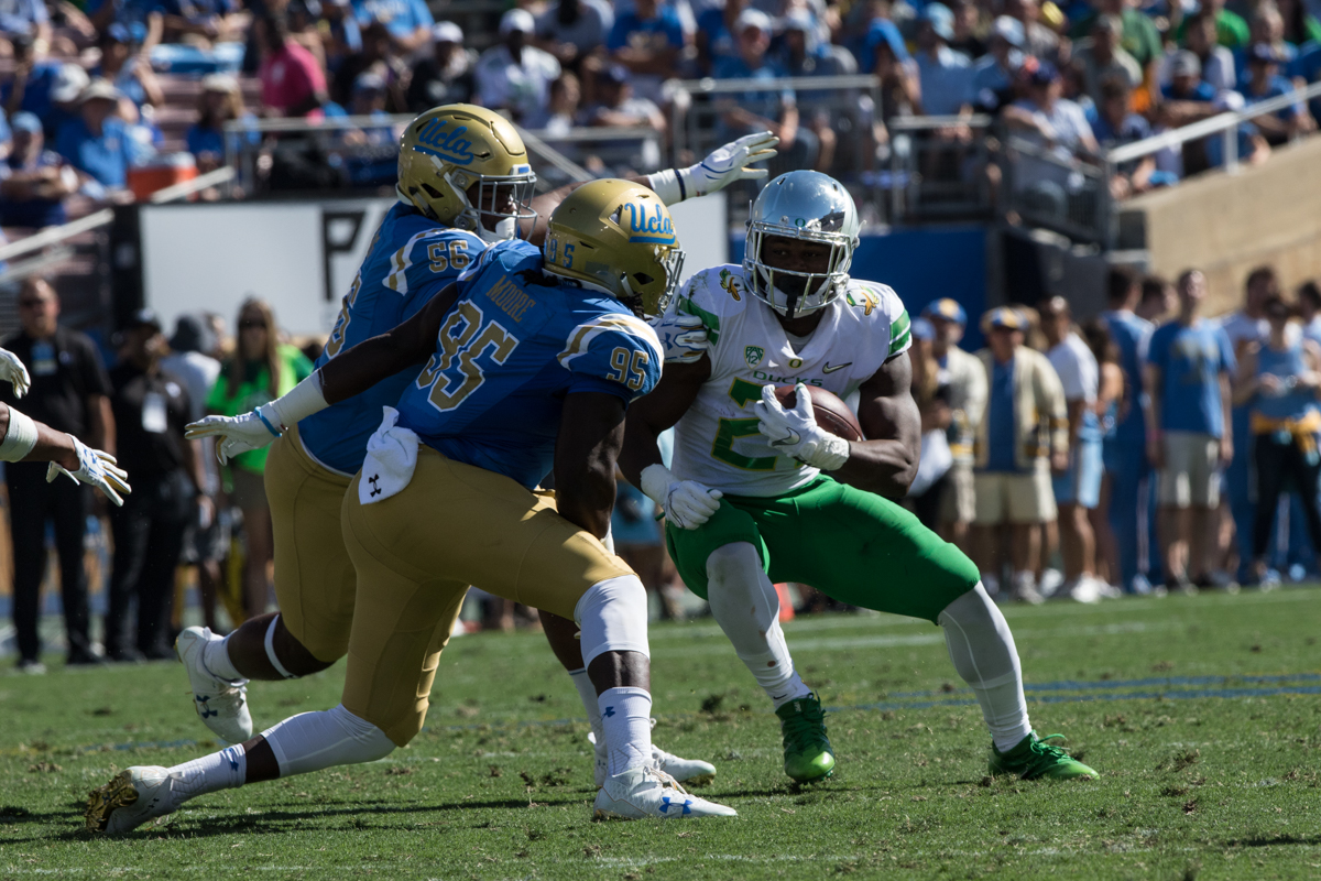Oregon running back Royce Freeman (#21) runs into two UCLA defenders. The Oregon Ducks rallied during the second quarter to go into halftime tied 14-14 with the UCLA Bruins at Rose Bowl Stadium in Pasadena, California. Photo by Austin Hicks, Oregon News Lab