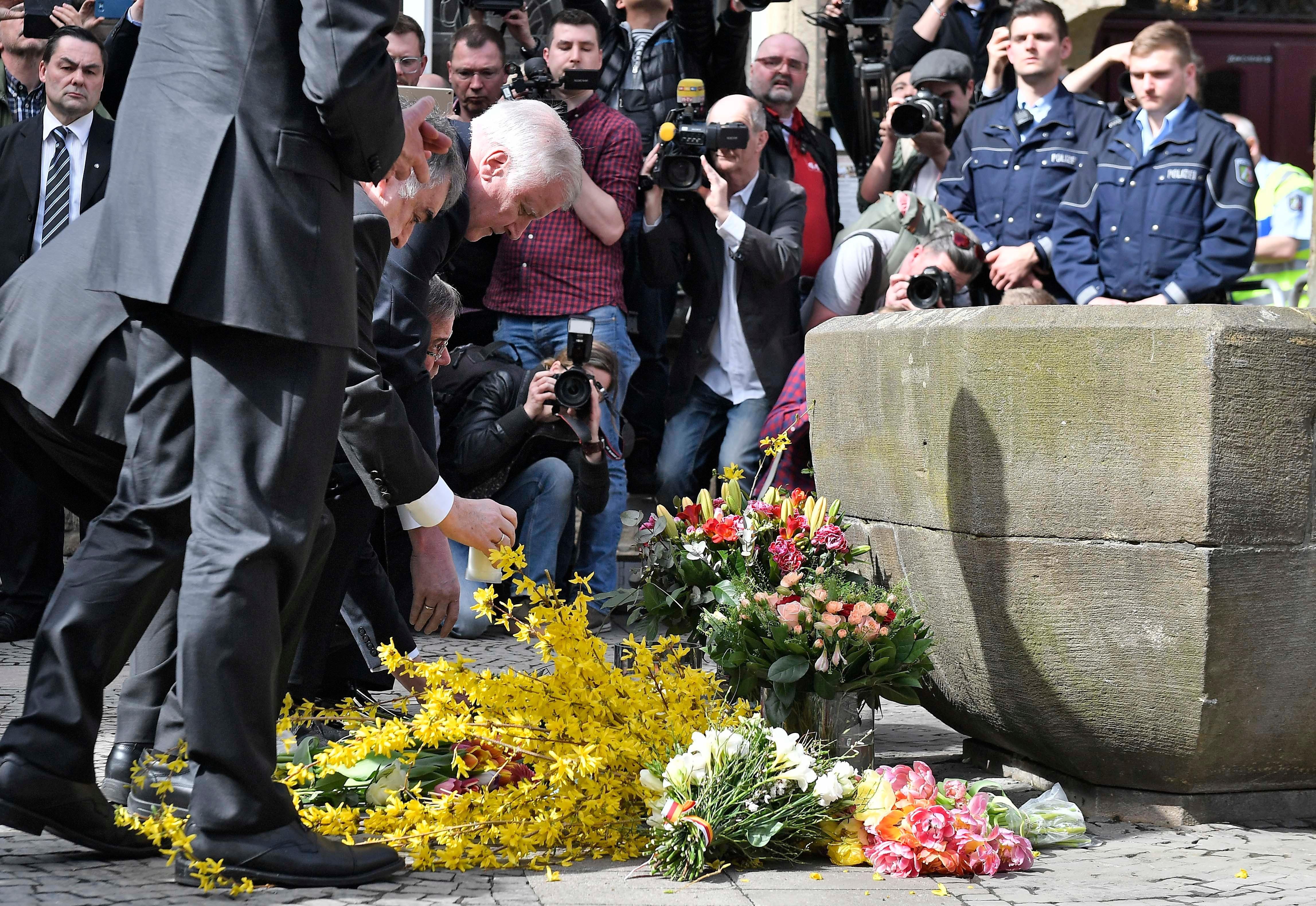 German interior minister Horst Seehofer places flowers at the place in Muenster, Germany, Sunday, April 8, 2018 where a vehicle crashed into a crowd yesterday. A van crashed into people drinking outside a popular bar Saturday in the German city of Muenster, killing two people and injuring 20 others before the driver of the vehicle shot and killed himself inside it, police said. (AP Photo/Martin Meissner)