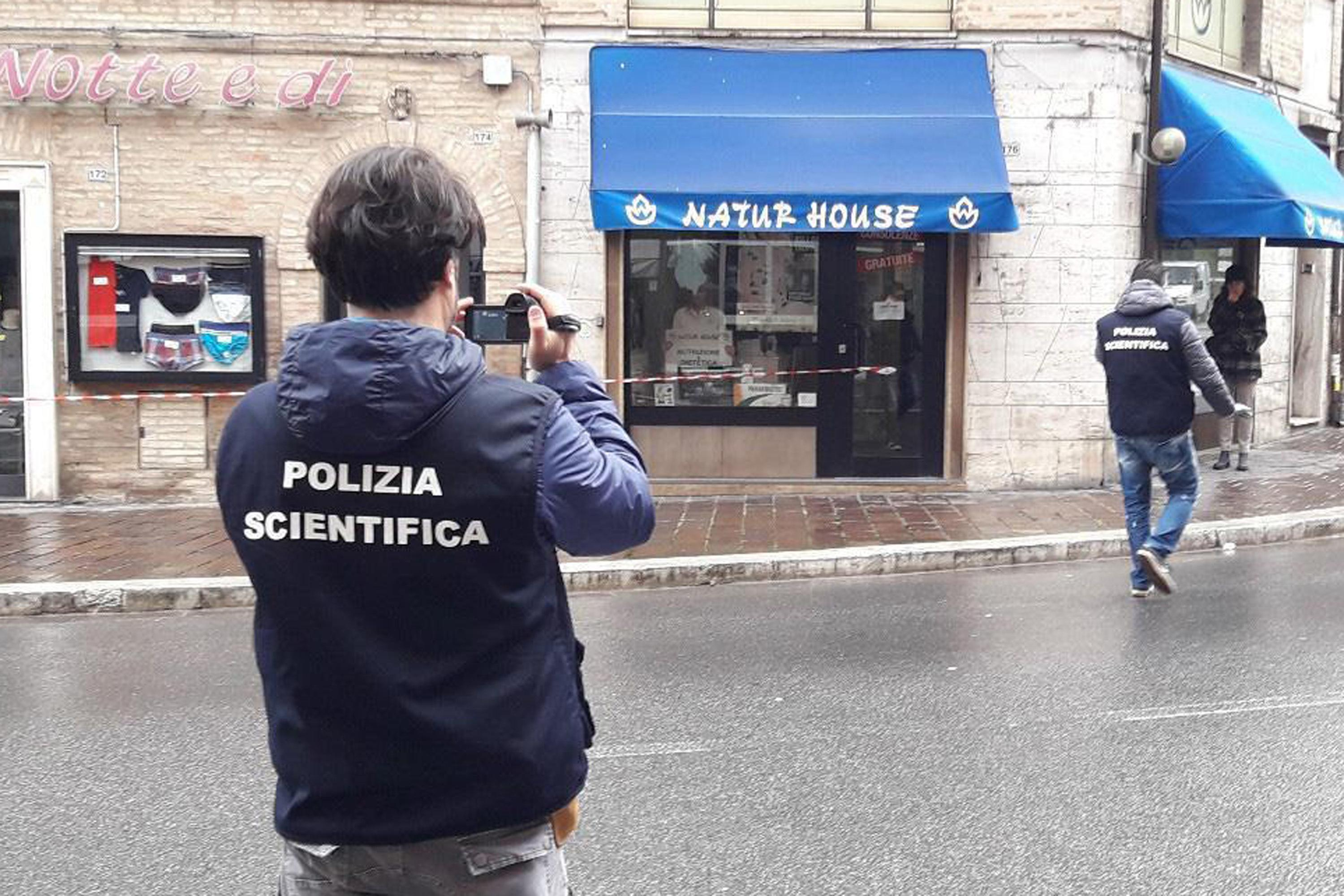 Italian Forensic policemen take pictures to the site of a shooting which broke out in Macerata, Italy, Saturday, Feb. 3, 2018. A lone gunman opened fire on foreigners in drive-by shootings in a central Italian city, wounding an undisclosed number of people Saturday morning before being arrested, police said. The suspect's motive wasn't immediately clear, but the city of Macerata is still reeling from the gruesome killing of a young Italian woman this week, allegedly at the hands of a Nigerian immigrant. (Carotti/ANSA via AP)