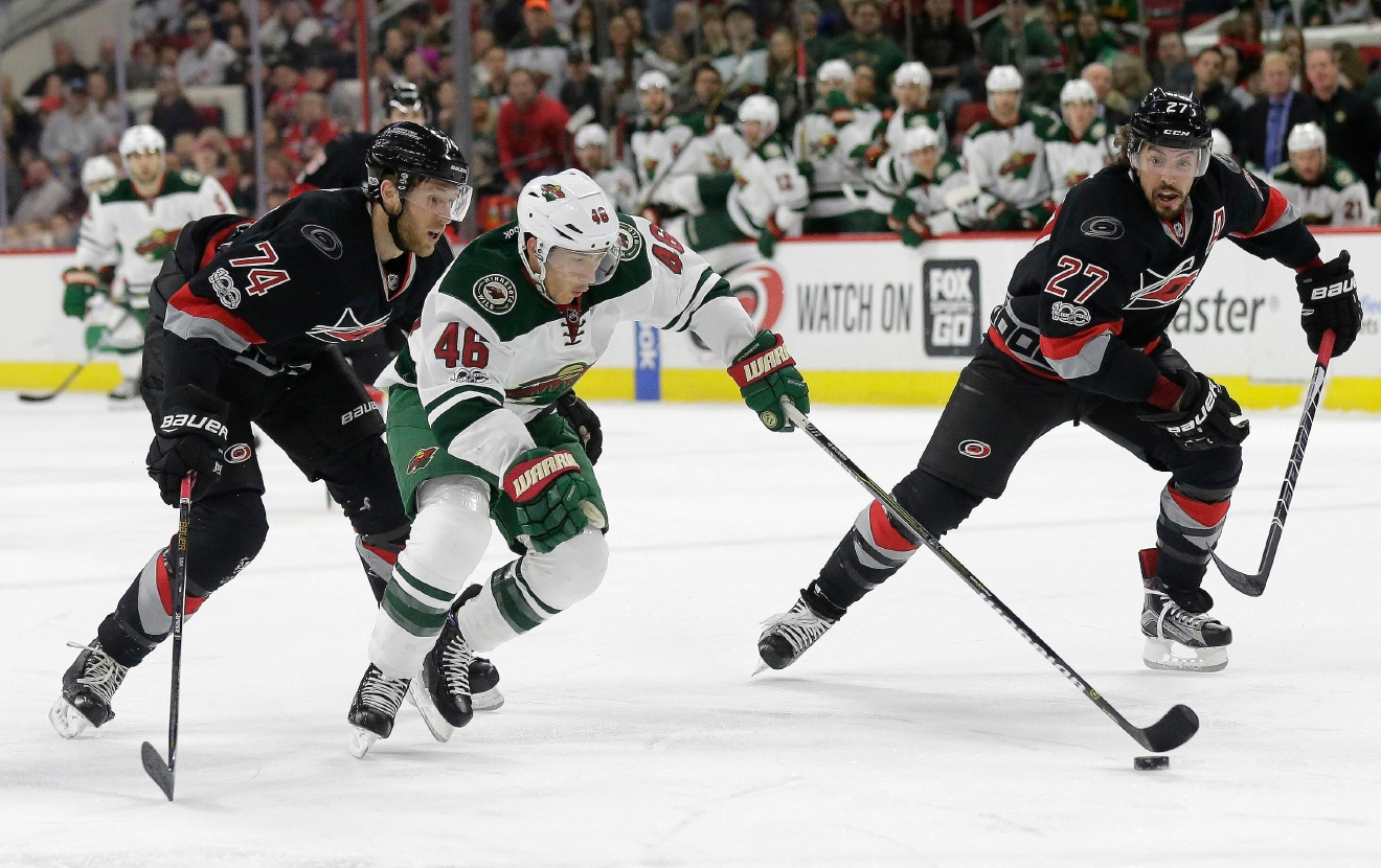 Carolina Hurricanes' Jaccob Slavin (74) and Justin Faulk (27) defend against Minnesota Wild's Jared Spurgeon (46) during the first period of an NHL hockey game in Raleigh, N.C., Thursday, March 16, 2017. (AP Photo/Gerry Broome)