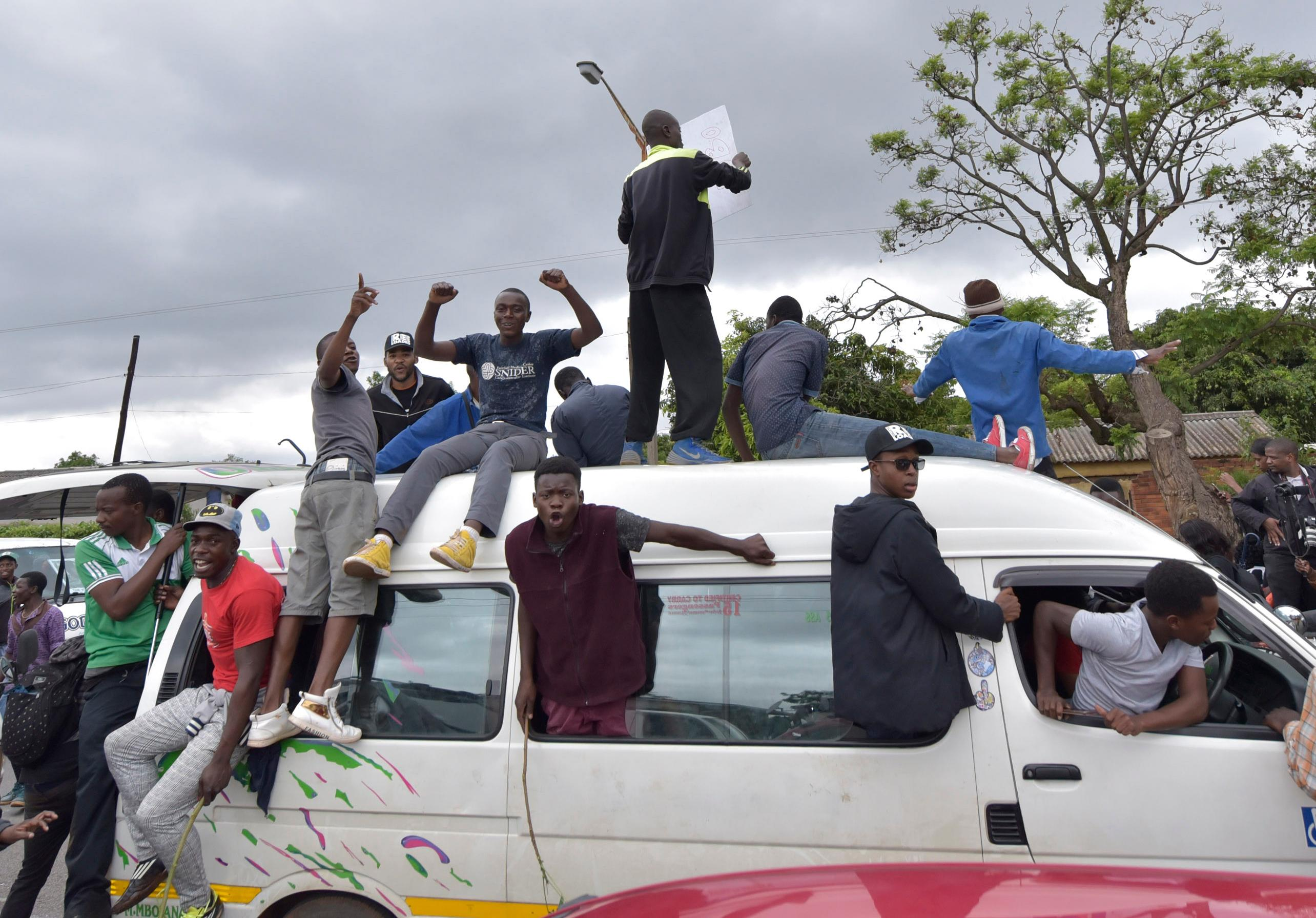 People cheer from the roof of a vehicle as euphoric crowds of several thousand people gathered in Zimbabwe's capital, Harare Saturday, Nov. 18, 2017 to demand the departure of President Robert Mugabe after nearly four decades in power. The 93-year-old Mugabe, the world's oldest head of state, is said to be asking for more time amid negotiations with regional leaders that seek his exit with a veneer of dignity. (AP Photo)