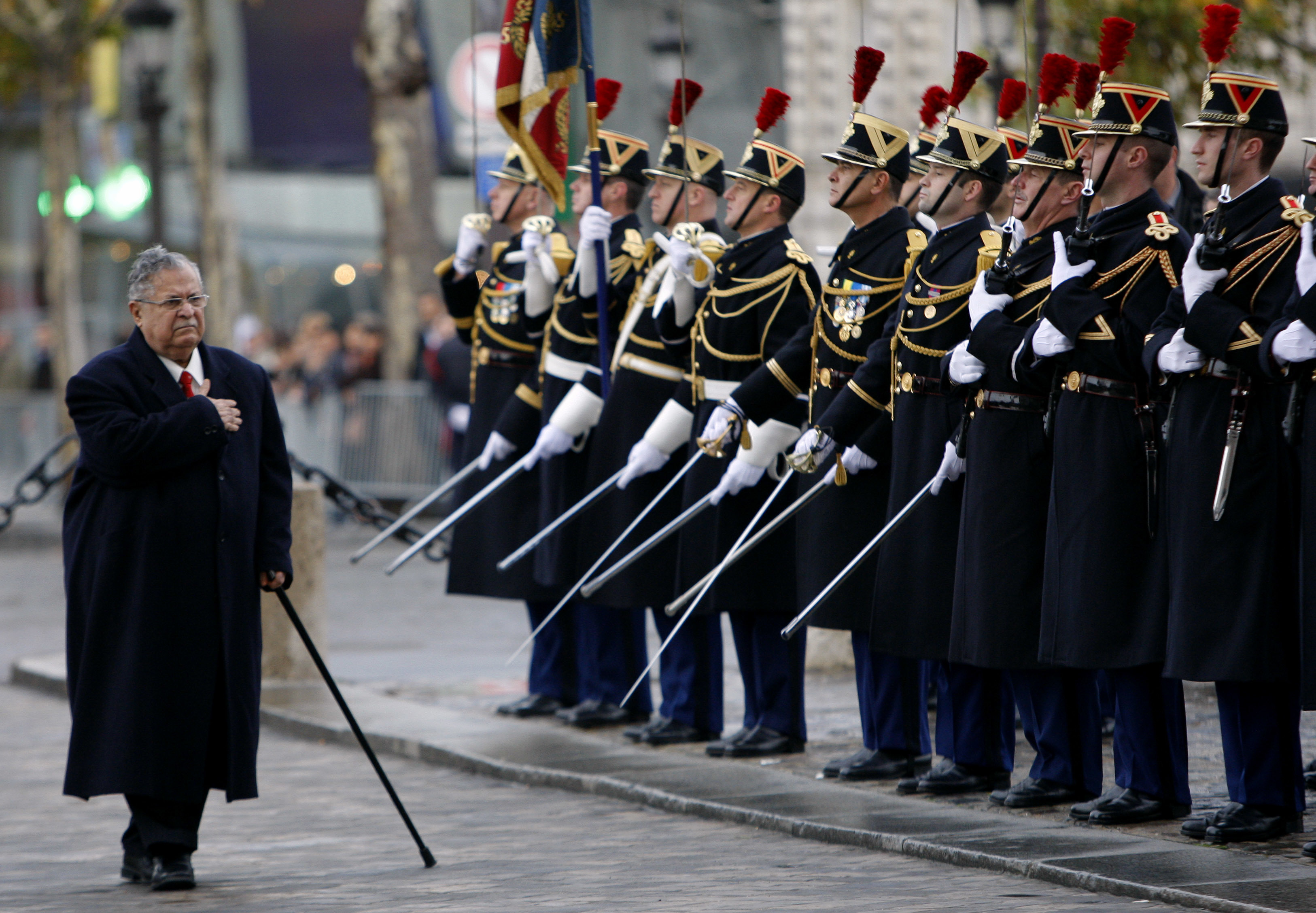 FILE - In this Nov. 17, 2009 file photo, then Iraqi President Jalal Talabani, center, reviews French troops at the Tomb of the Unknown Soldier, in Paris,France. Talabani, a lifelong fighter for Iraq's Kurds who rose to become the country's president, presenting himself as a unifying father figure to temper the potentially explosive hatreds among Kurds, Shiites and Sunnis has died in a Berlin hospital at the age of 83. (AP Photo/Christophe Ena, pool)