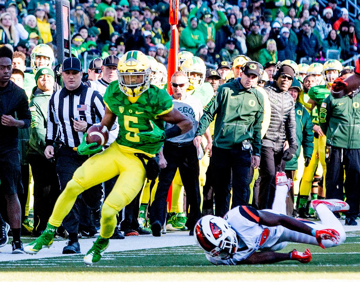 Oregon Ducks Taj Griffin (#5) slips away from the Oregon State Beavers defense to go in for a score in the Civil War game in Autzen Stadium. At the half the Ducks led the Beavers 31 - 7. Photo by Katie Pietzold, Oregon News Lab