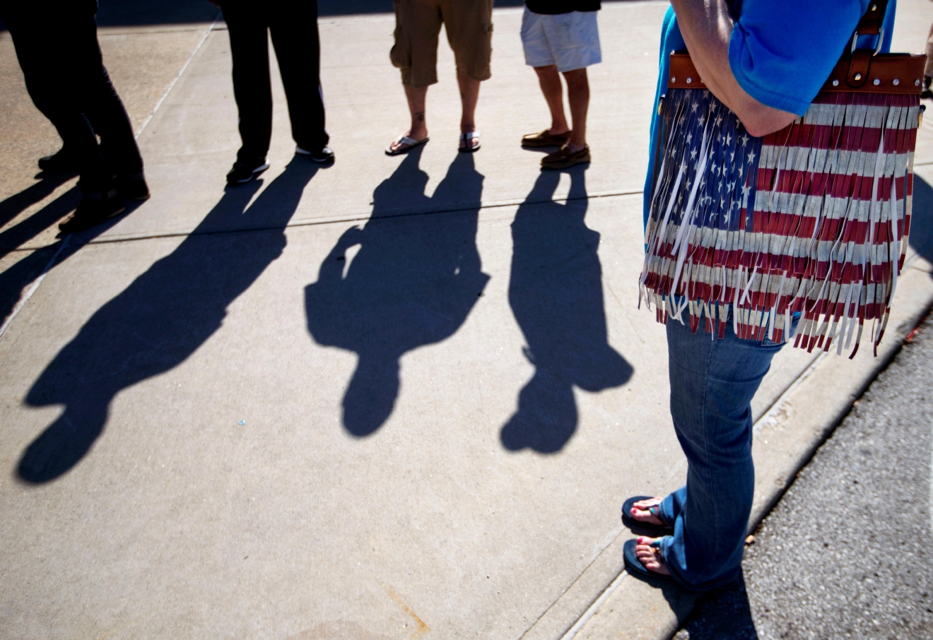 Stephanie Roby, right, of Louisville, stands with an American flag-themed bag while waiting in line for the ticket office to open for tickets for Muhammad Ali's Jenazah service at Freedom Hall Tuesday, June 7, 2016, in Louisville, Ky. The day before his star-studded funeral, members of Ali's Islamic faith will get their chance to say a traditional goodbye during a Jenazah, a traditional Muslim funeral. (AP Photo/David Goldman)