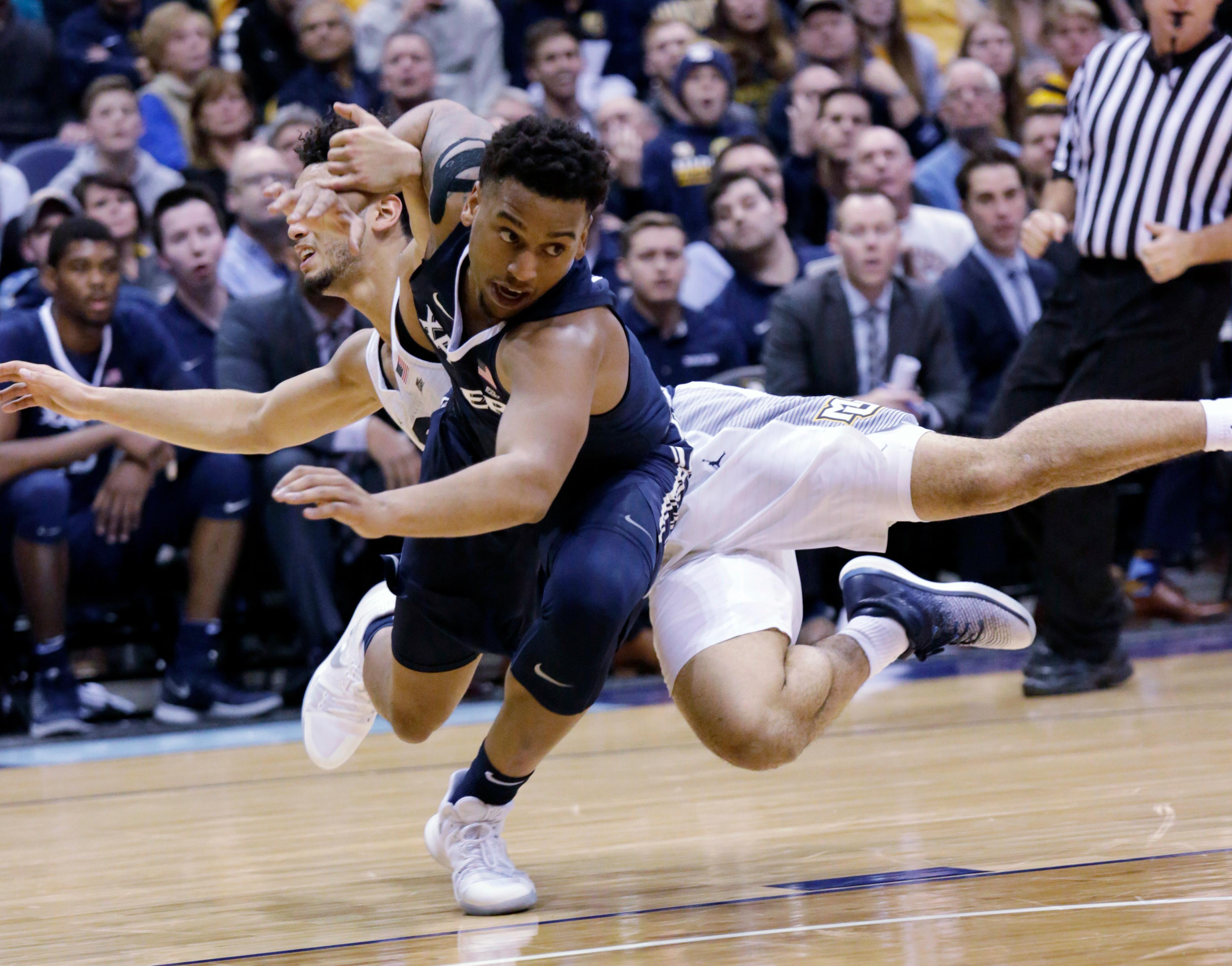 Xavier guard Trevon Bluiett, front, is fouled by Marquette guard Markus Howard during the first half of a basketball game, Wednesday, Dec. 27, 2017, in Milwaukee. (AP Photo/Darren Hauck)