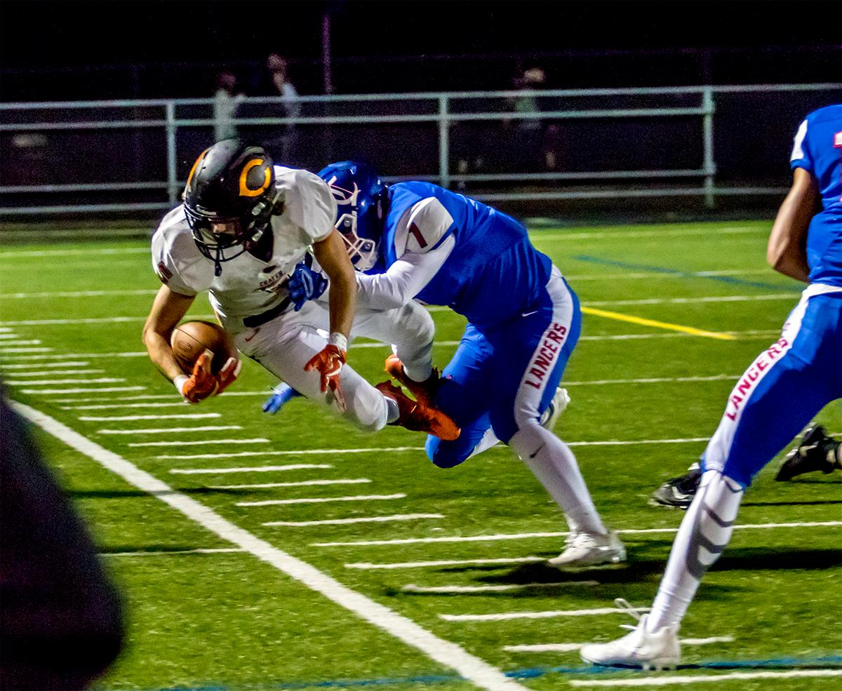 Churchill's Beau Burnett (#1) knocks Crater's Cade Weaver (#5) out of bounds. Churchill defeated Crater 63-21 on Friday at their homecoming game. Churchill remains undefeated with a conference record of 9-0. Photo by August Frank, Oregon News Lab