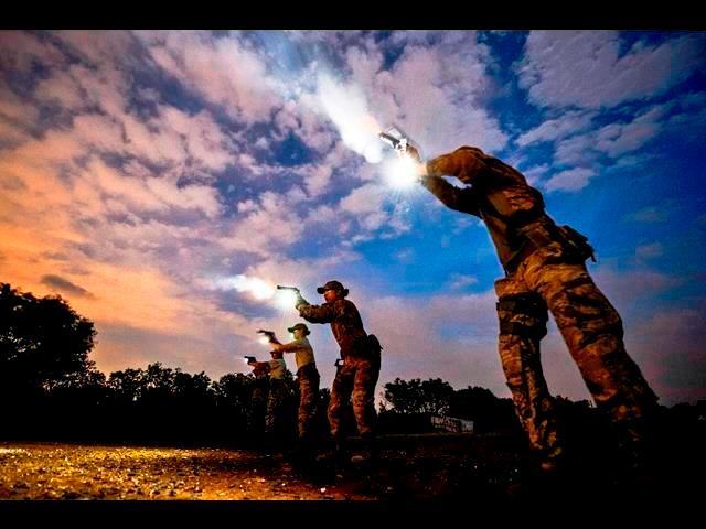 Air Force Senior Airman Cory Payne uses a flash light while firing an M9 Beretta during an advanced weapons course at a shooting range in Atascosa, Texas, May 7, 2014.