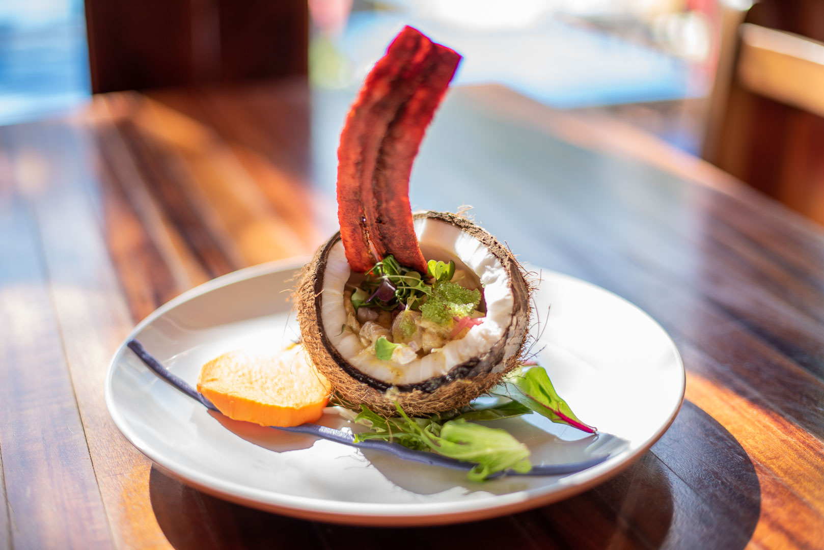 The menu at the breezy, beachy boîte features favorites from an array of sunny ports – from conch fritters and ceviche served in a coconut to an ahi tuna poke tower and jerk chicken. (Image: Courtesy Tortuga)