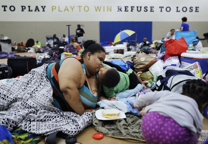 <p>FILE - In this Sept. 9, 2017, file photo, Annette Davis kisses her son Darius, 3, at a shelter in Miami, after evacuating from their home in Florida City, Fla., ahead of Hurricane Irma. The year's biggest news stories chronicled an historic hurricane season that had Florida in its crosshairs. Hurricane Irma knocked out power for millions across wide swaths of the state on both coasts, from Key West to Jacksonville, left homes destroyed and lives disrupted. (AP Photo/David Goldman, File)</p>