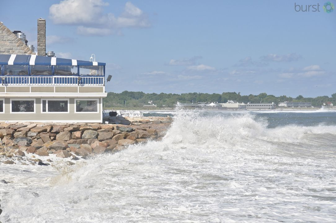 Other pictures show waves crashing along the Coast Guard House, a restaurant located along the beach.