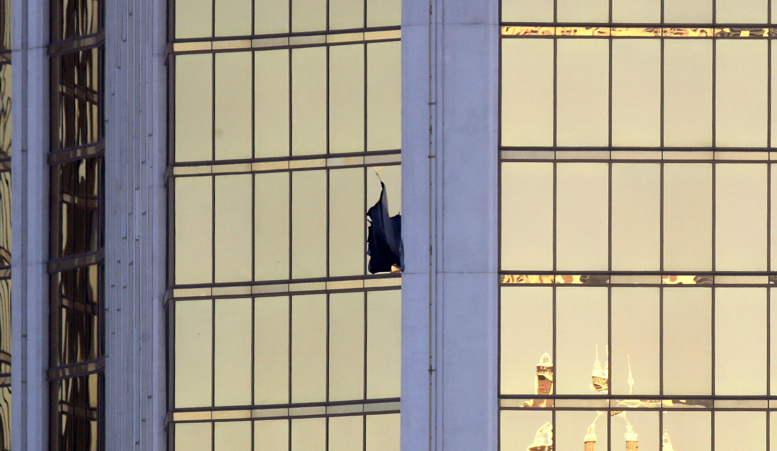 A broken window is seen at the Mandalay Bay resort and casino Monday, Oct. 2, 2017, on the Las Vegas Strip following a mass shooting at a music festival in Las Vegas. Authorities say Stephen Craig Paddock broke the window and began firing with a cache of weapons, killing dozens and injuring hundreds. (AP Photo/Chris Carlson)
