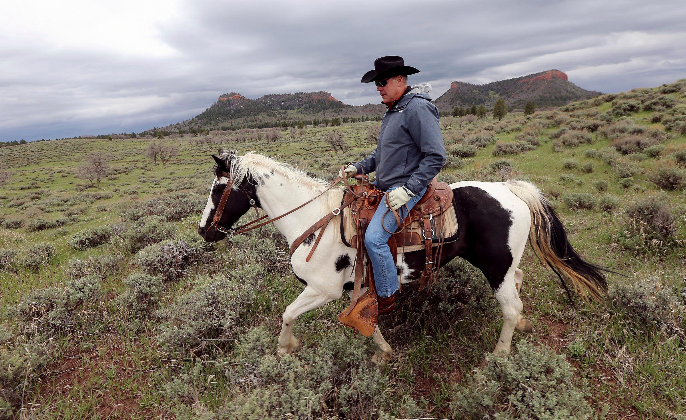 FILE - In this May 9, 2017, file photo, Interior Secretary Ryan Zinke rides a horse in the new Bears Ears National Monument near Blanding, Utah. Utah has long stood out for going far beyond other Western states in trying to get back control of its federally protected lands. When President Donald Trump on Monday, Dec. 4, 2017, announces he's going to shrink two national monuments in the state, his warm welcome will stand out in a region that is normally protective of its parks and monuments. (Scott G Winterton/The Deseret News via AP, File)