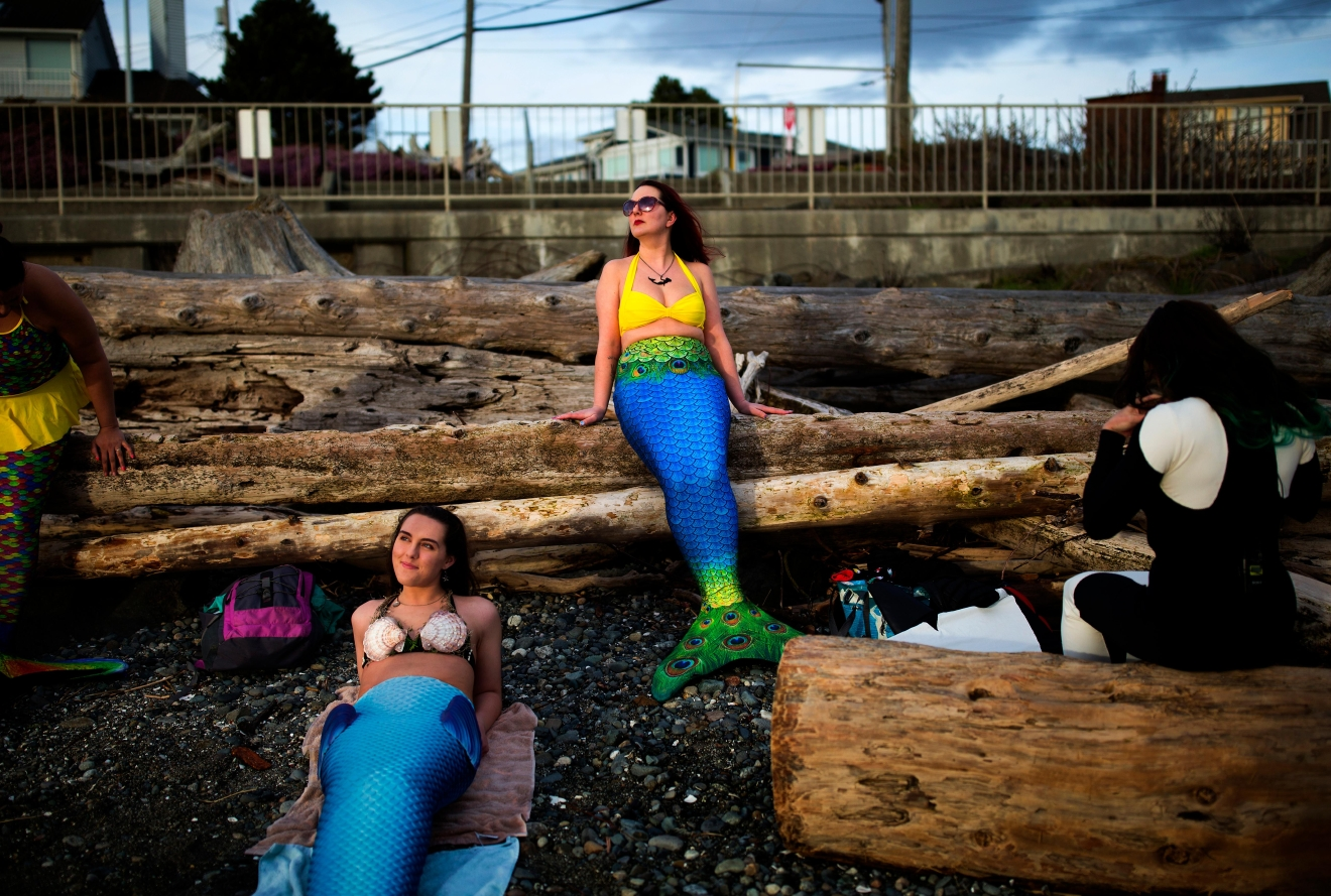 Emily Beckley, right, and Brianna Parise, left, lay on driftwood during a photoshoot with Seattle Refined. (Sy Bean / Seattle Refined)