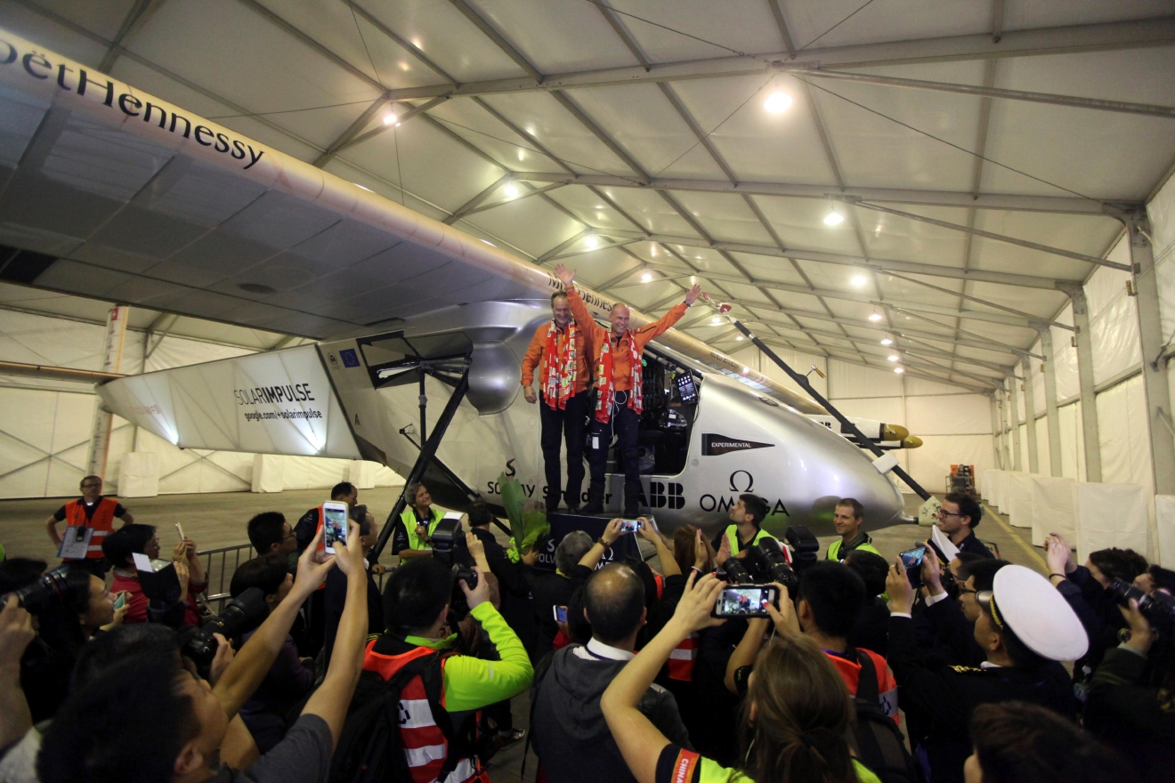 FILE - In this March 31, 2015 file photo, pilots Andre Boschberg, center left, and Bertrand Piccard, at right, pose for photos with their solar powered plane in a hangar at Chongqing Jiangbei International Airport in southwest China's Chongqing Municipality.  The solar-powered airplane landed in California on Saturday, April 23, 2016, completing a risky, three-day flight across the Pacific Ocean as part of its journey around the world.  (AP Photo/File)