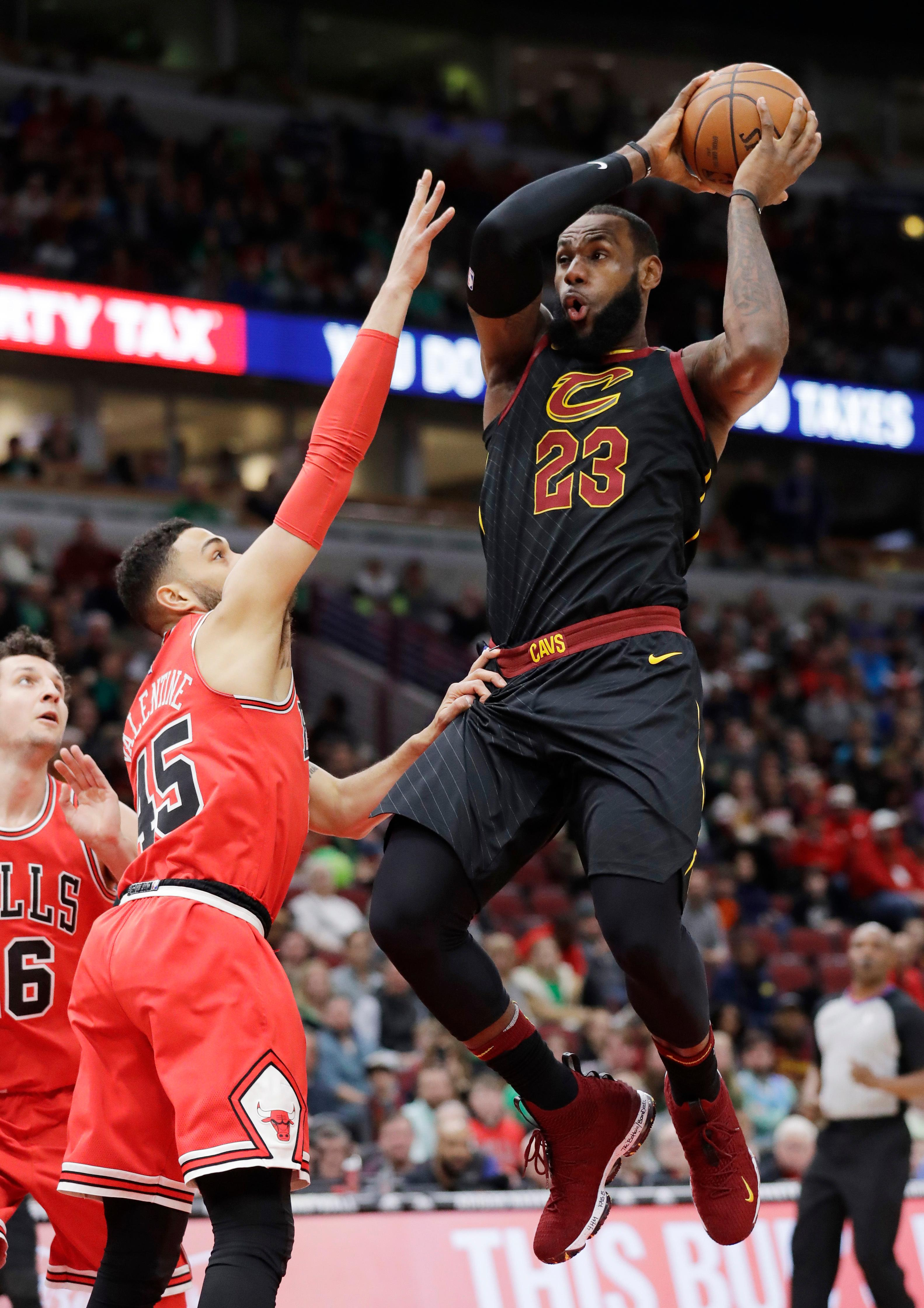 Cleveland Cavaliers forward LeBron James, right, drives to the basket against Chicago Bulls guard Denzel Valentine, center, and forward Paul Zipser during the first half of an NBA basketball game Saturday, March 17, 2018, in Chicago. (AP Photo/Nam Y. Huh)