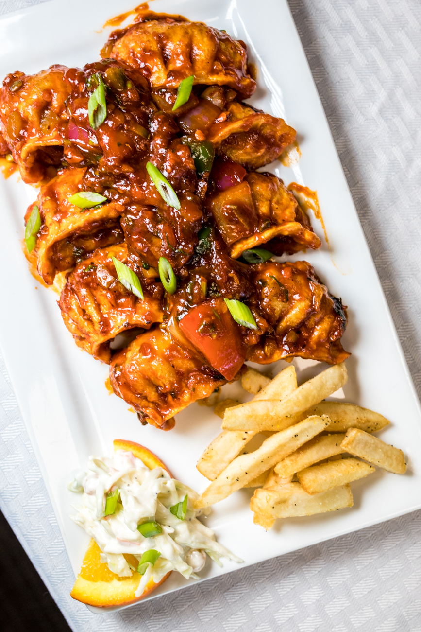 Chili Manchurian Mo:Mo: the momos are fried and tossed in a wok with Manchurian chili sauce and served with a mixed salad, fries, and chutney / Image: Catherine Viox{ }// Published: 2.6.20