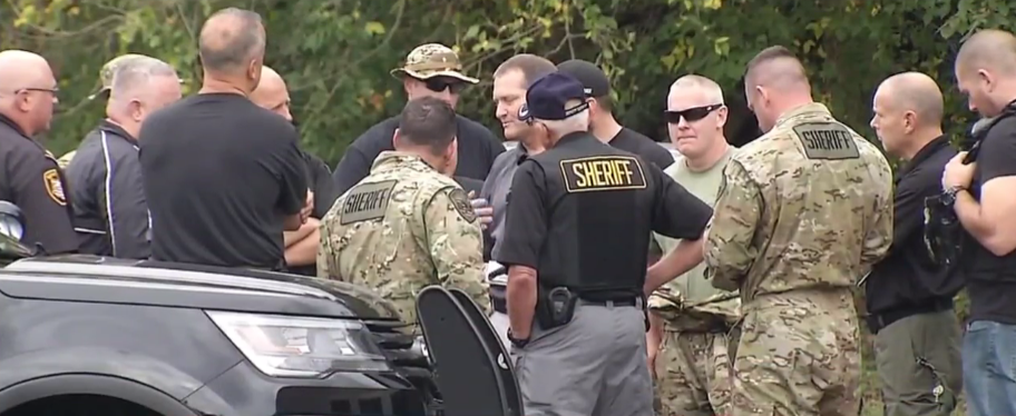 Law enforcement officers involved in a massive manhunt in a quadruple murder investigation in Lawrence County, Ohio, gather Thursday. Authorities are following up on tips in the search for suspect Aaron Lawson, 23. (WCHS/WVAH)