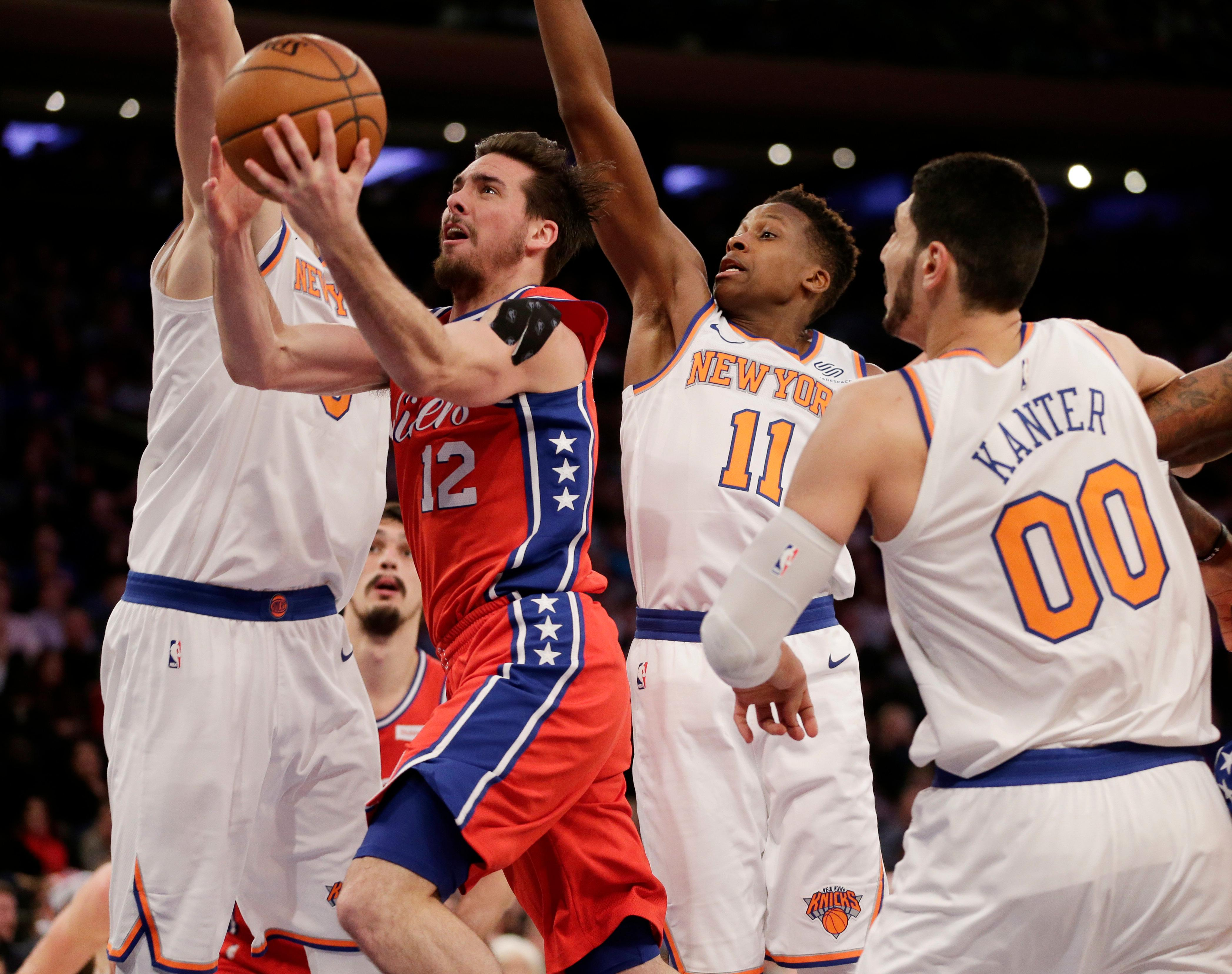 Philadelphia 76ers' T.J. McConnell, second from left, drives to the basket through New York Knicks defenders during the second half of the NBA basketball game, Monday, Dec. 25, 2017, in New York. The 76ers defeated the Knicks 105-98. (AP Photo/Seth Wenig)