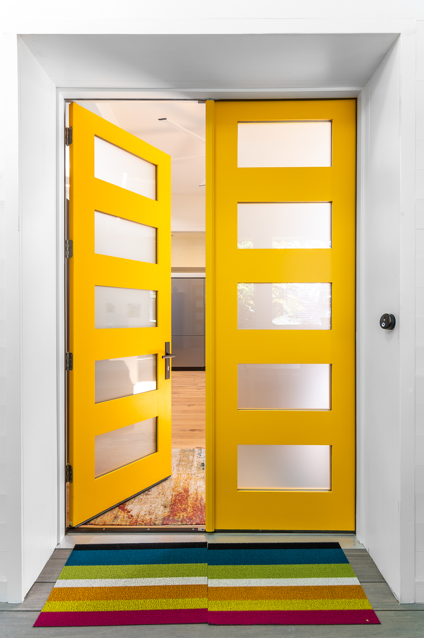 Striking yellow French doors lead into the home. / Image: Phil Armstrong // Published: 10.11.20