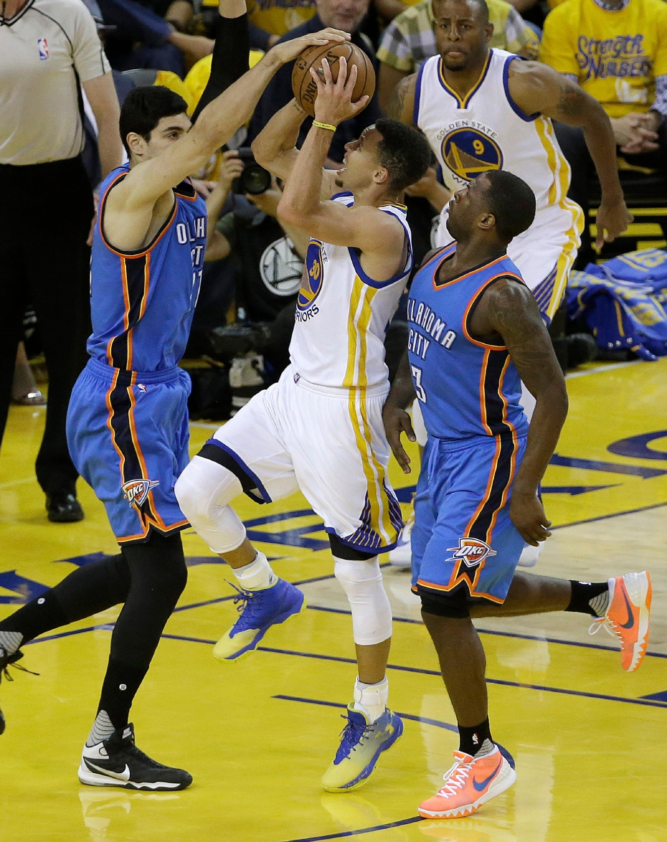 Golden State Warriors guard Stephen Curry, center, shoots between Oklahoma City Thunder center Enes Kanter, left, and guard Dion Waiters during the first half of Game 2 of the NBA basketball Western Conference finals in Oakland, Calif., Wednesday, May 18, 2016. (AP Photo/Jeff Chiu)