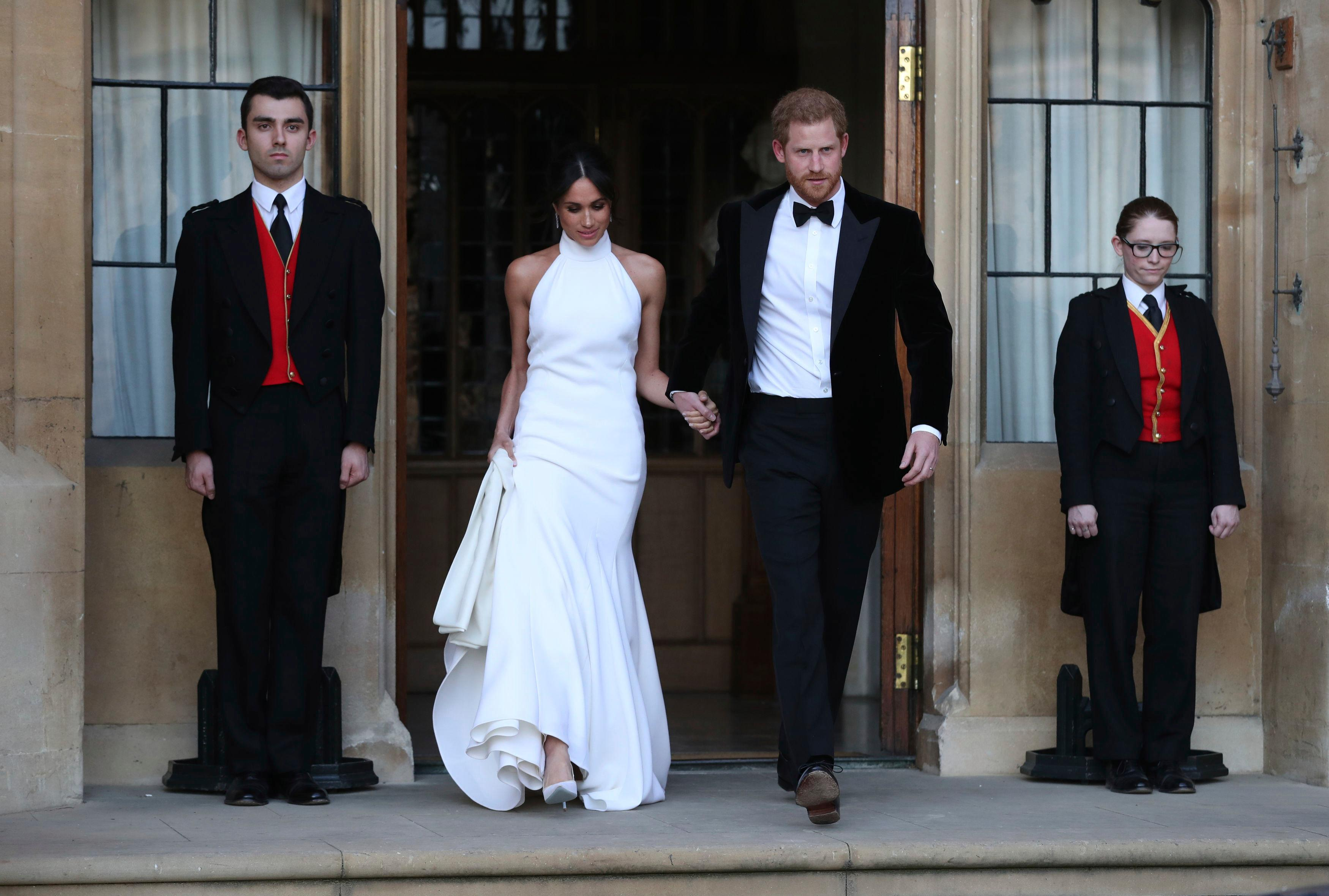 The newly married Duke and Duchess of Sussex, Meghan Markle and Prince Harry, leave Windsor Castle after their wedding in Windsor, England, to attend an evening reception at Frogmore House, hosted by the Prince of Wales, Saturday, May 19, 2018. (Steve Parsons/pool photo via AP)