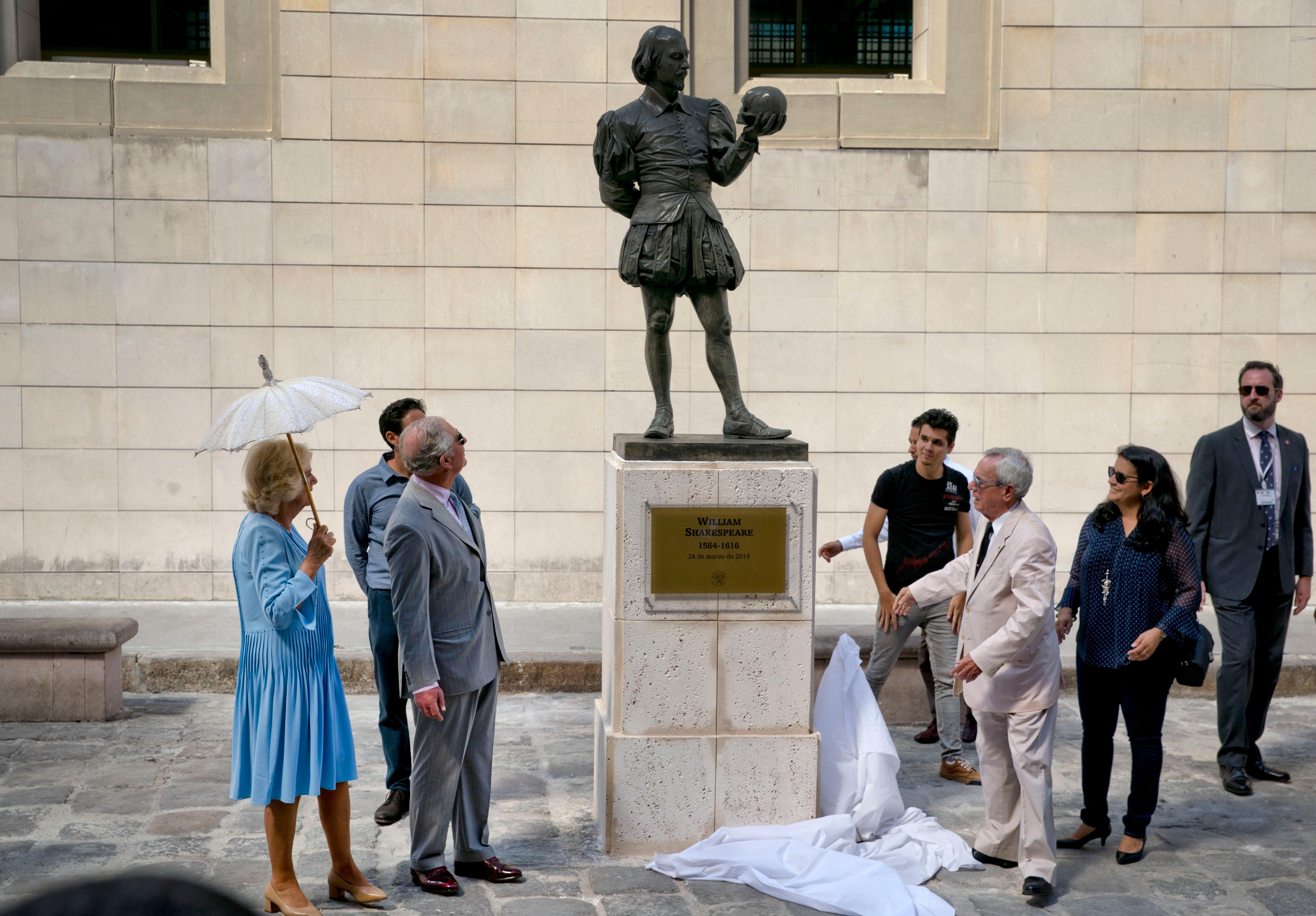 Britain's Prince Charles, the Prince of Wales, second from left, and his wife Camilla, Duchess of Cornwall, with umbrella, reveal a statue of William Shakespeare during a guided tour by City Historian Eusebio Leal, front right, as they tour the historic area of Havana, Cuba, Monday, March 25, 2019. (AP Photo/Ramon Espinosa)