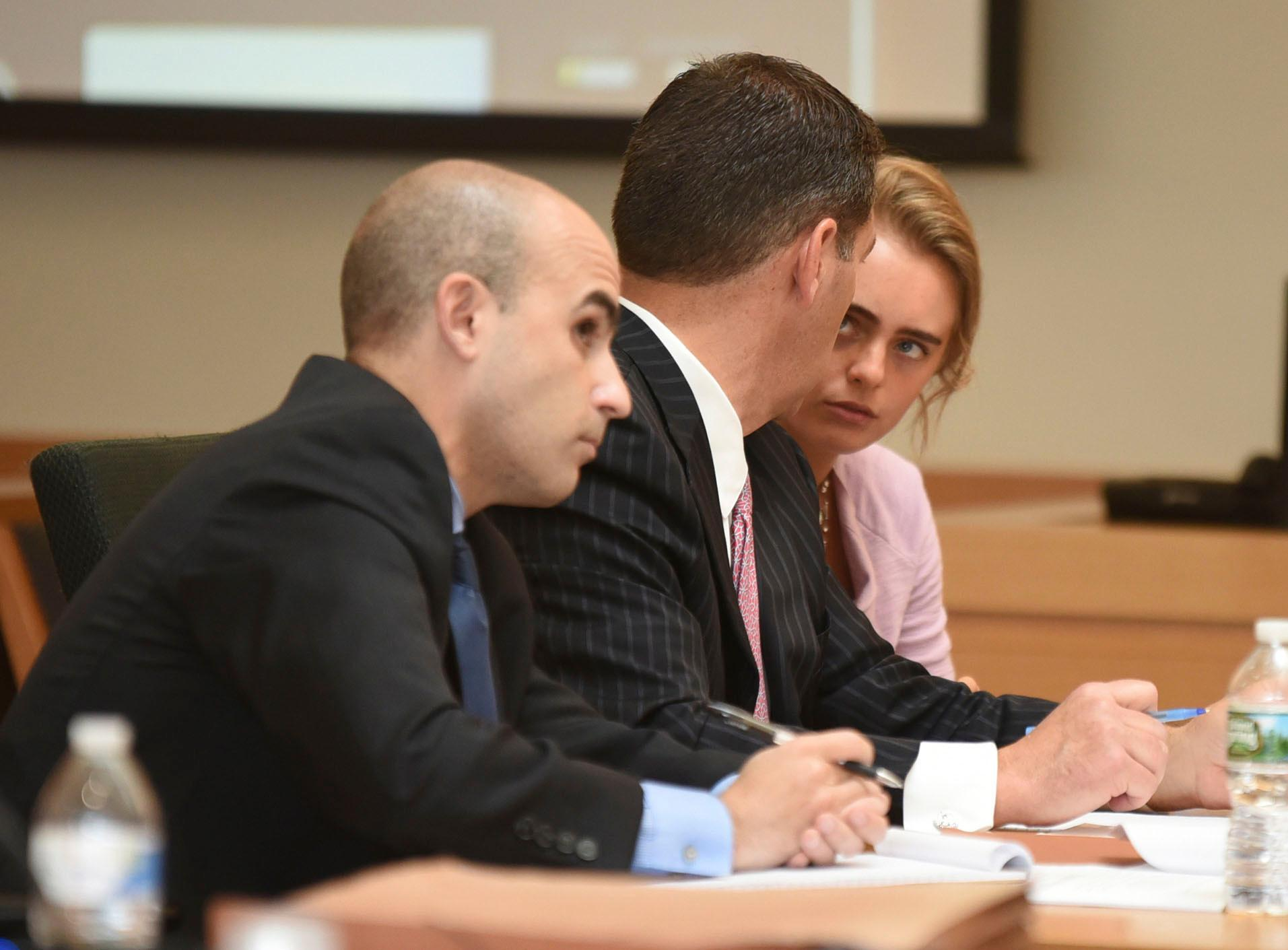 Michelle Carter, right, listens to her attorney Joseph Cataldo, center, as defense attorney Cory Madera looks on in Taunton Juvenile Court on Friday, June 9, 2017. A judge has denied a request for a not-guilty verdict by an attorney for Carter who is charged with involuntary manslaughter for allegedly convincing her boyfriend to kill himself through a series of text messages. (Glenn Silva/Fairhaven Neighborhood News/Pool via AP)