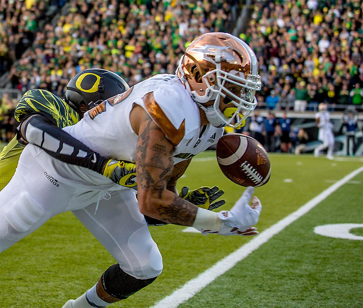The Sun Devils' Jalen Harvey (#82) goes for a catch as a Ducks player tackles him. The Oregon Ducks broke their losing streak by defeating the ASU Sun Devils on Saturday 54-35. Photo by August Frank, Oregon News Lab