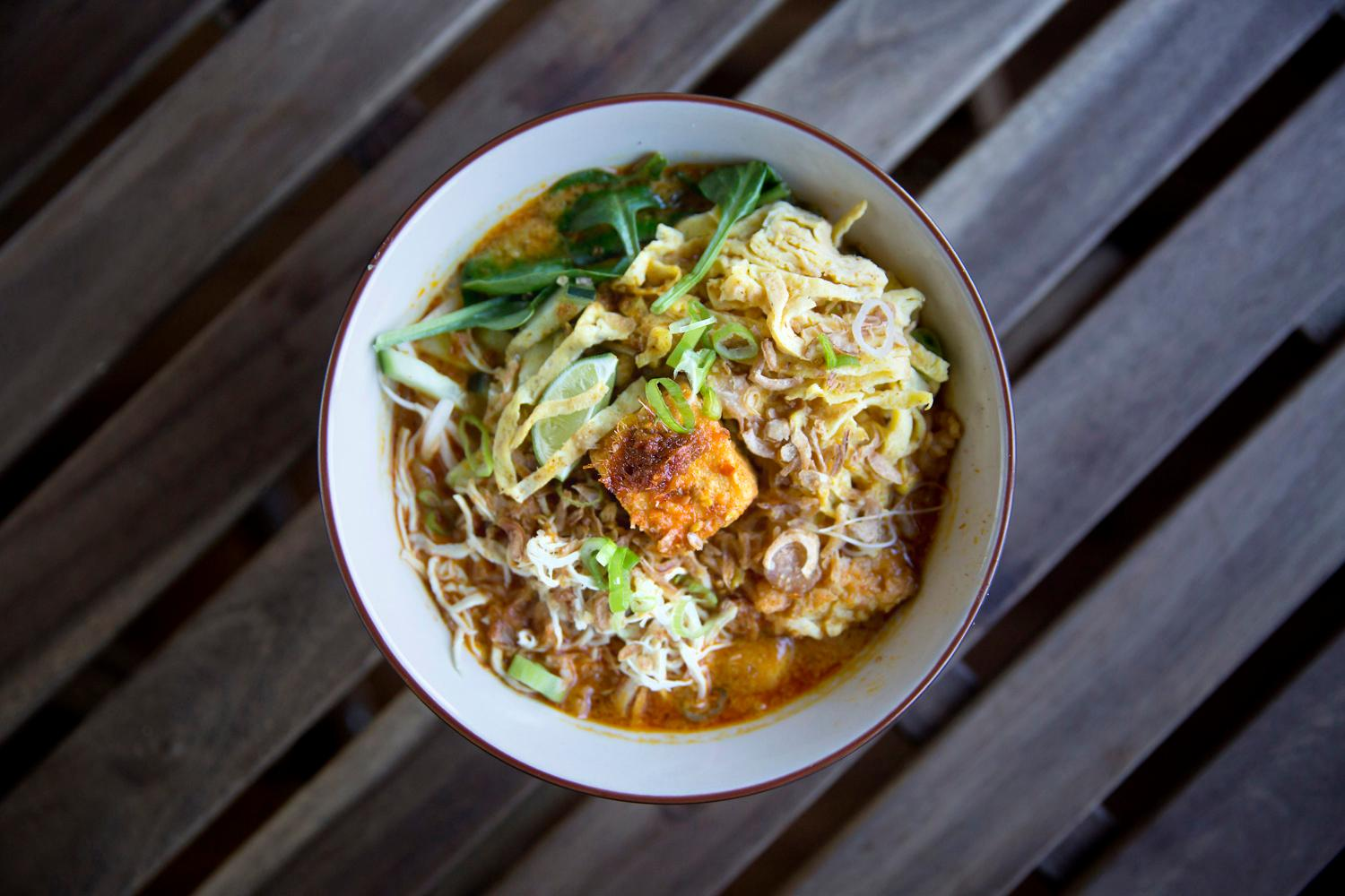 Nyonya Laksa - noodles in creamy coconut milk curry-like gravy with Manila clam, jumbo shripms, tofu puffs, organic hard-boiled eggs, sprinkled with cucumber and Daun Kesum, at Reunion Malaysian Cafe & Kitchen, located at 339 Kirkland Ave C, in Kirkland. (Sy Bean / Seattle Refined)