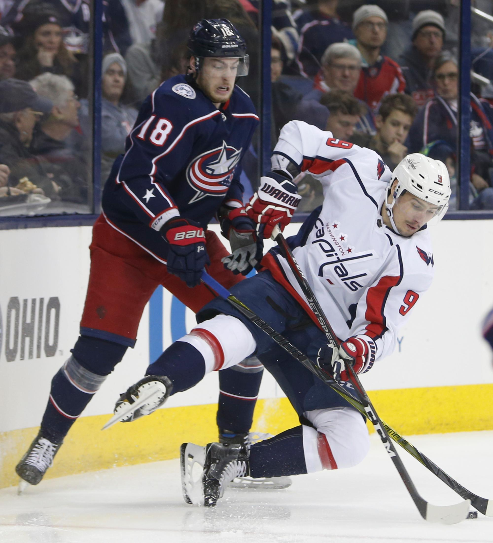 Columbus Blue Jackets' Pierre-Luc Dubois, left, and Washington Capitals' Dmitry Orlov, of Russia, fight for a loose puck during the second period of an NHL hockey game Tuesday, Feb. 6, 2018, in Columbus, Ohio. (AP Photo/Jay LaPrete)
