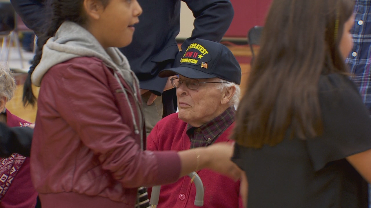 Several dozen veterans attended an assembly at Dayton High School to kick off Veterans Legacies, a program to preserve memories of World War II veterans. World War II vet Fred Hisaw (in red sweater) meets students and staff. (KATU)<p></p>