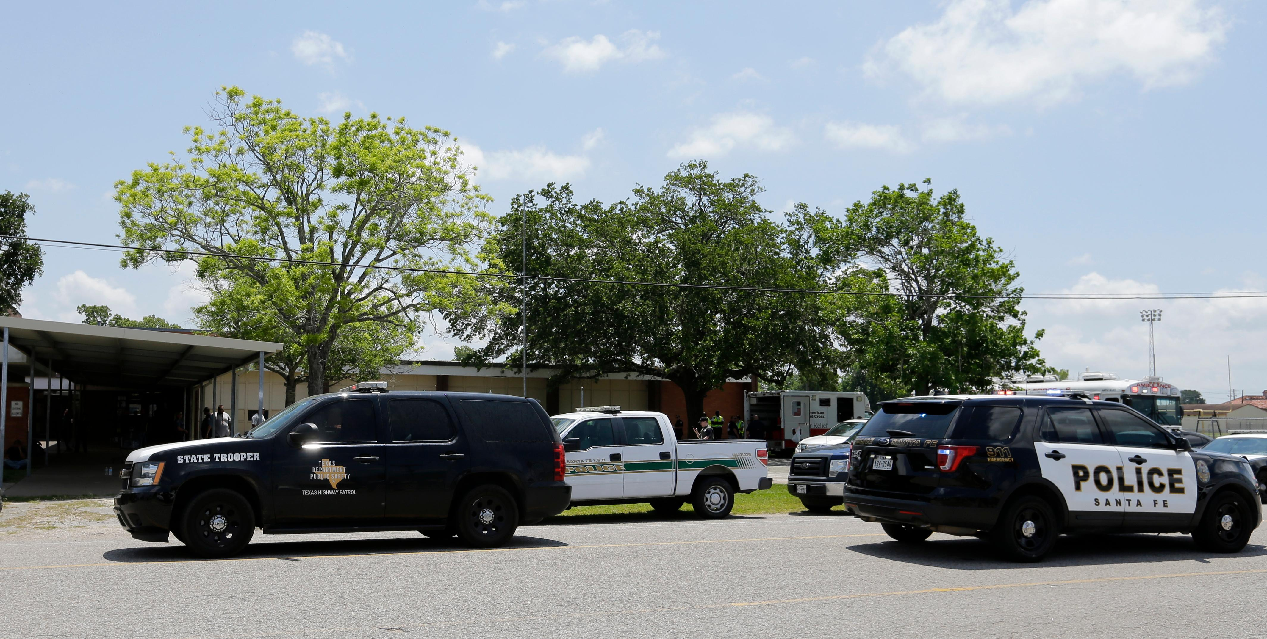 Law enforcement vehicles are parked outside the Alamo Gym where students and parents wait to reunite following a shooting at Santa Fe High School Friday, May 18, 2018, in Santa Fe, Texas. (AP Photo/David J. Phillip)