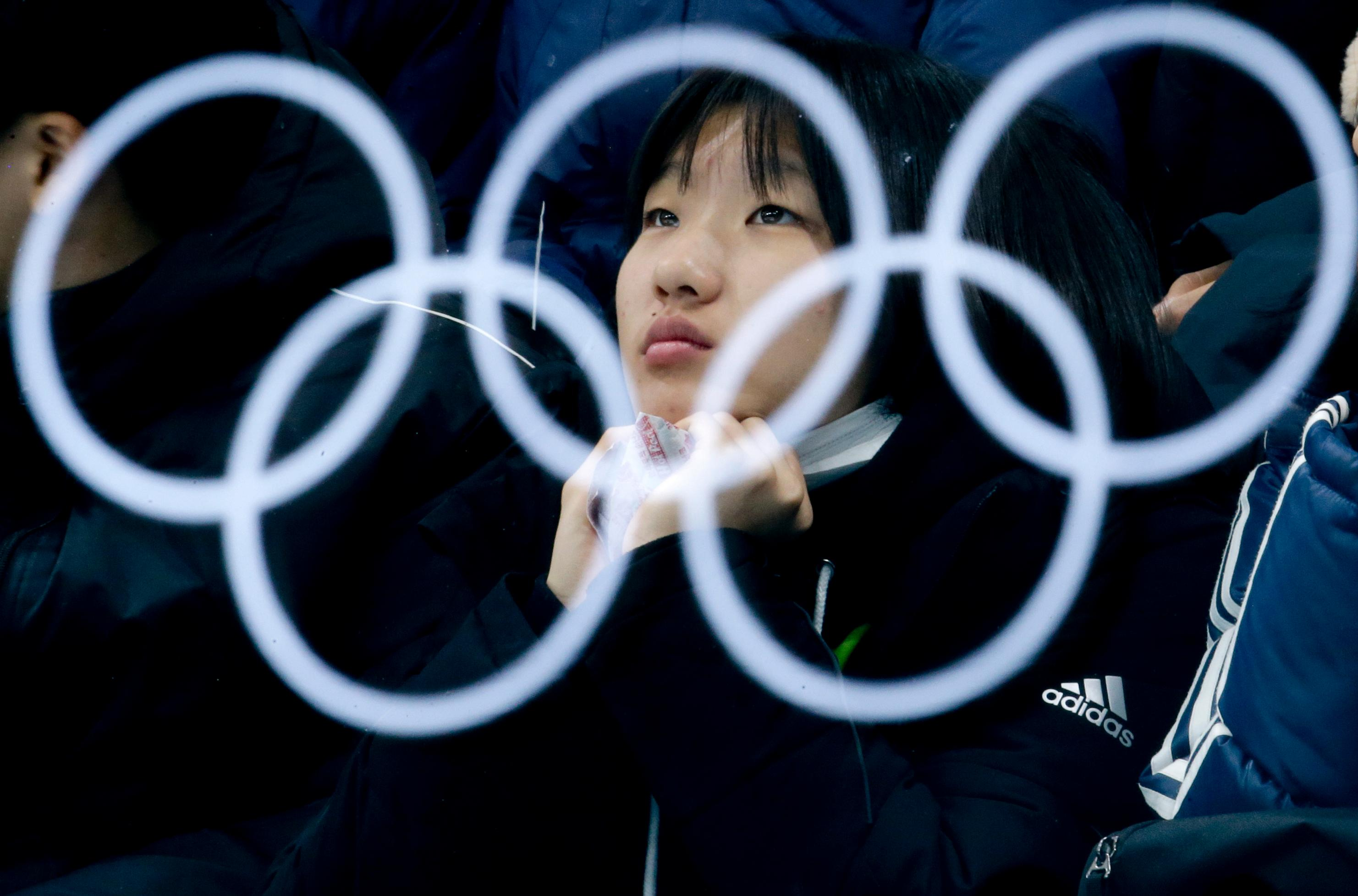 The Olympic rings are reflected in a glass as a spectator watches the mixed doubles semi-final curling match between Canada and Norway at the 2018 Winter Olympics in Gangneung, South Korea, Monday, Feb. 12, 2018. (AP Photo/Natacha Pisarenko)