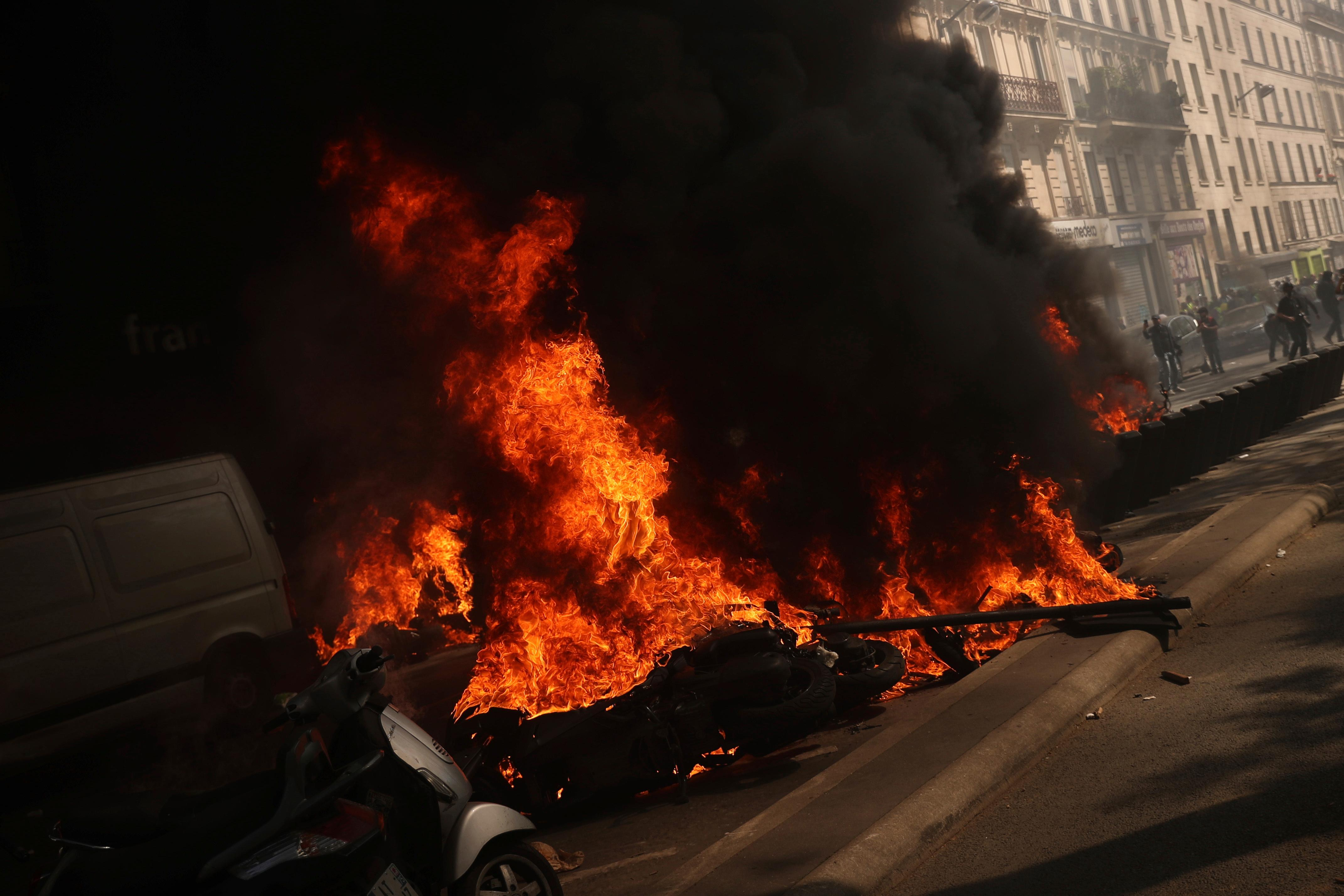 Motorbikes set alight during a yellow vest demonstration in Paris, Saturday, April 20, 2019. French yellow vest protesters are marching anew to remind the government that rebuilding the fire-ravaged Notre Dame Cathedral isn't the only problem the nation needs to solve. (AP Photo/Francisco Seco)