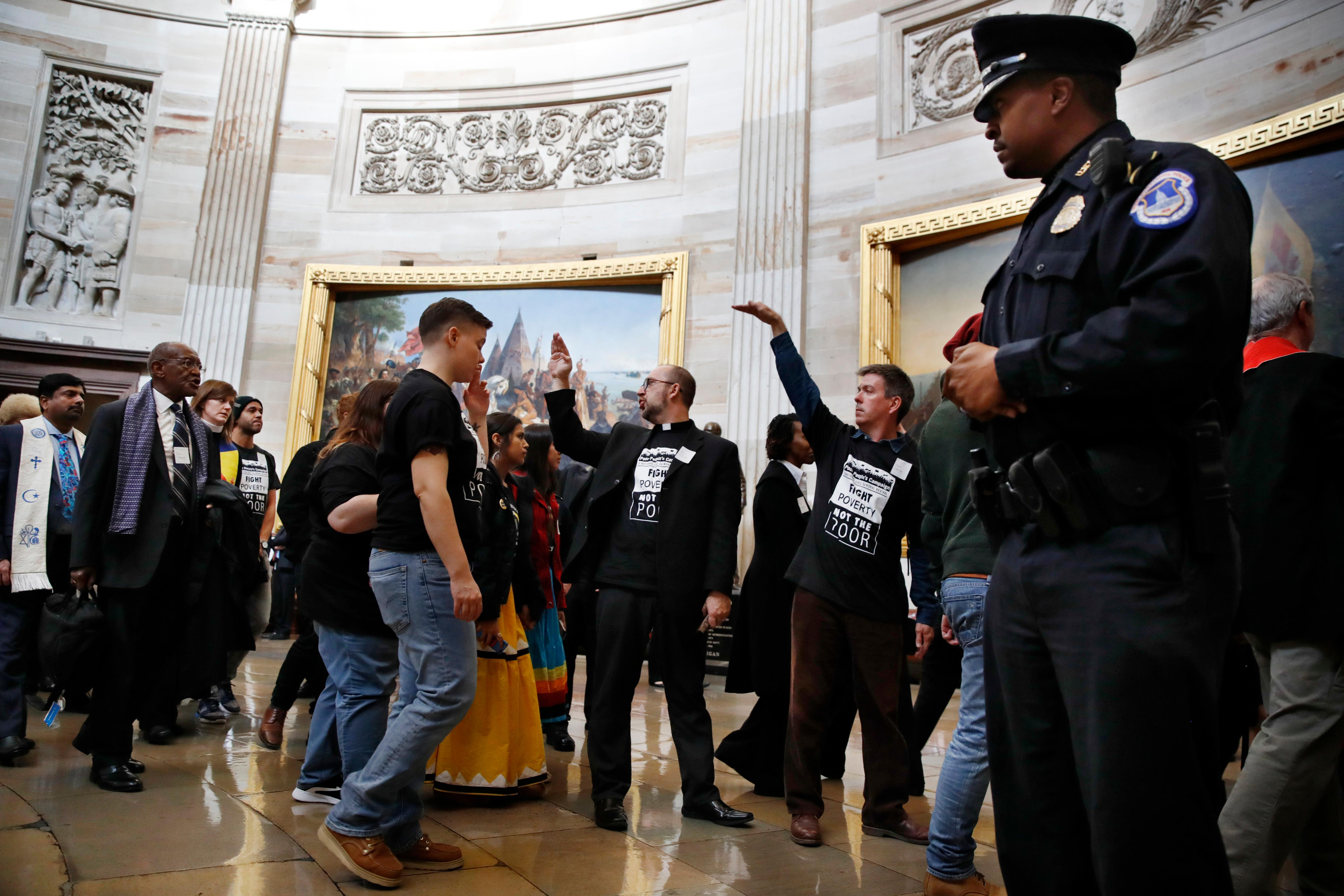 "With shirts saying ""fight poverty not the poor,"" people with the ""Poor People's Campaign"" gesture the group to remain quiet as the group leaves the Capitol Rotunda after praying in an act of civil disobedience in protest of the GOP tax overhaul, Monday, Dec. 4, 2017, on Capitol Hill in Washington. (AP Photo/Jacquelyn Martin)"