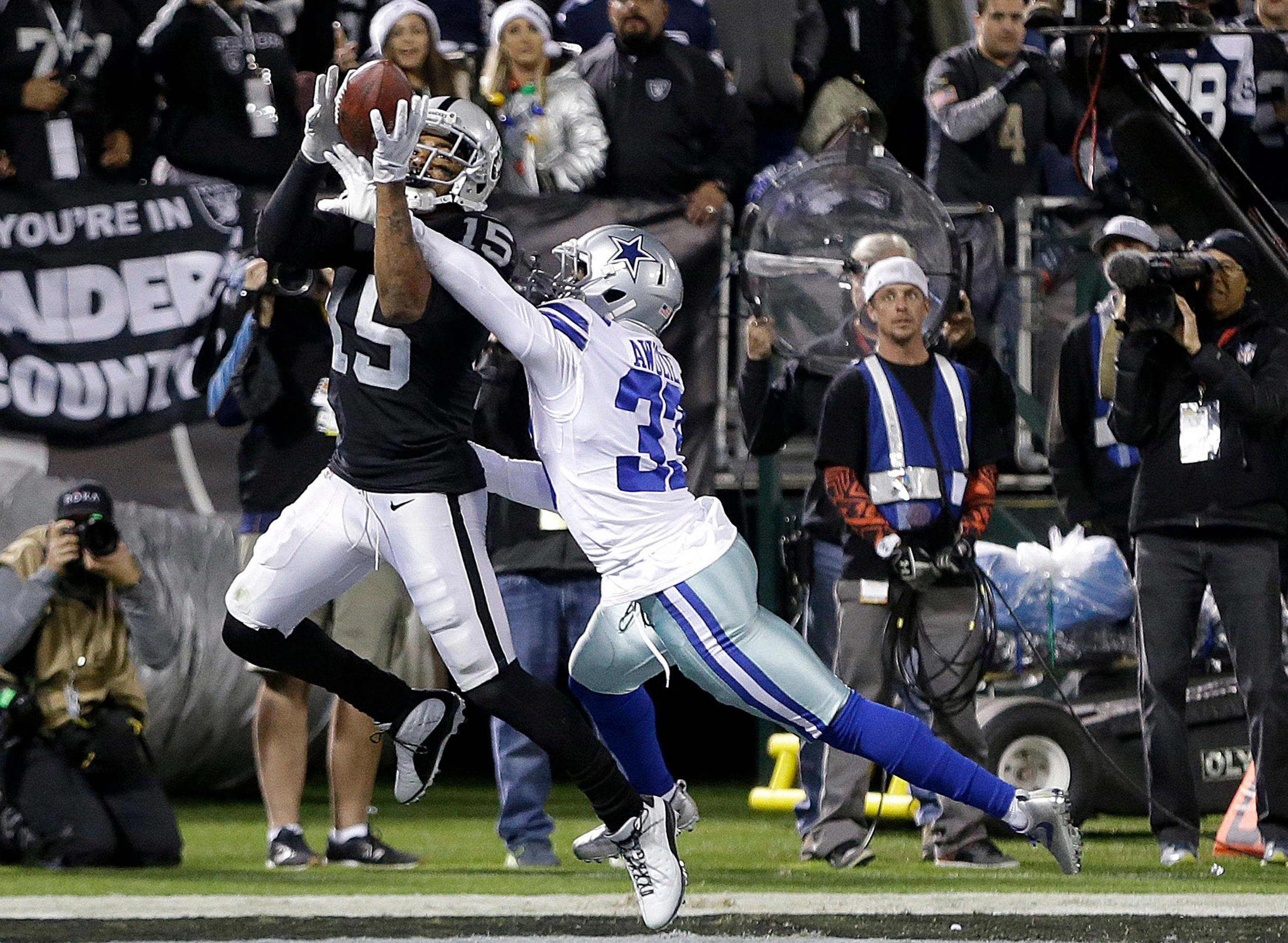 Oakland Raiders wide receiver Michael Crabtree (15) catches a touchdown pass in front of Dallas Cowboys cornerback Chidobe Awuzie (33) during the second half of an NFL football game in Oakland, Calif., Sunday, Dec. 17, 2017. (AP Photo/Ben Margot)