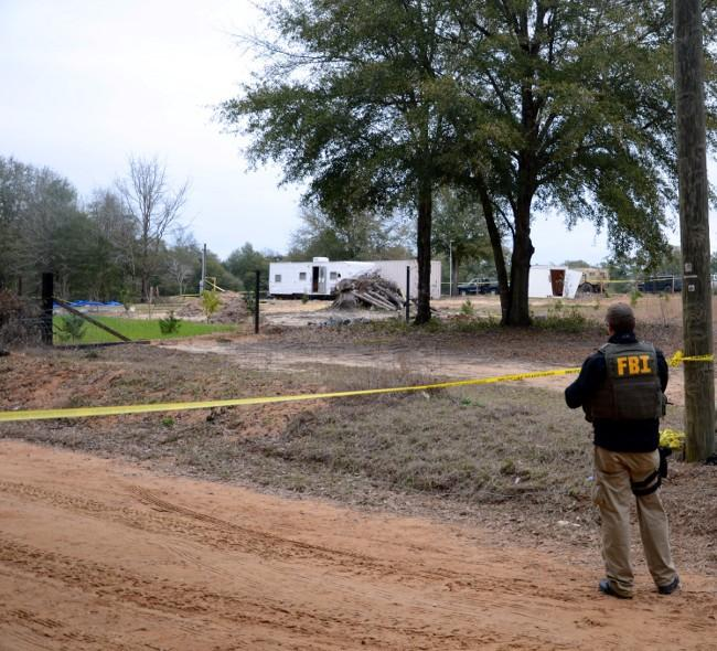 FBI agents and Dale County Sheriff%u2019s Deputies secure the residence where a 5-year-old child was rescued after being held hostage for almost one week.