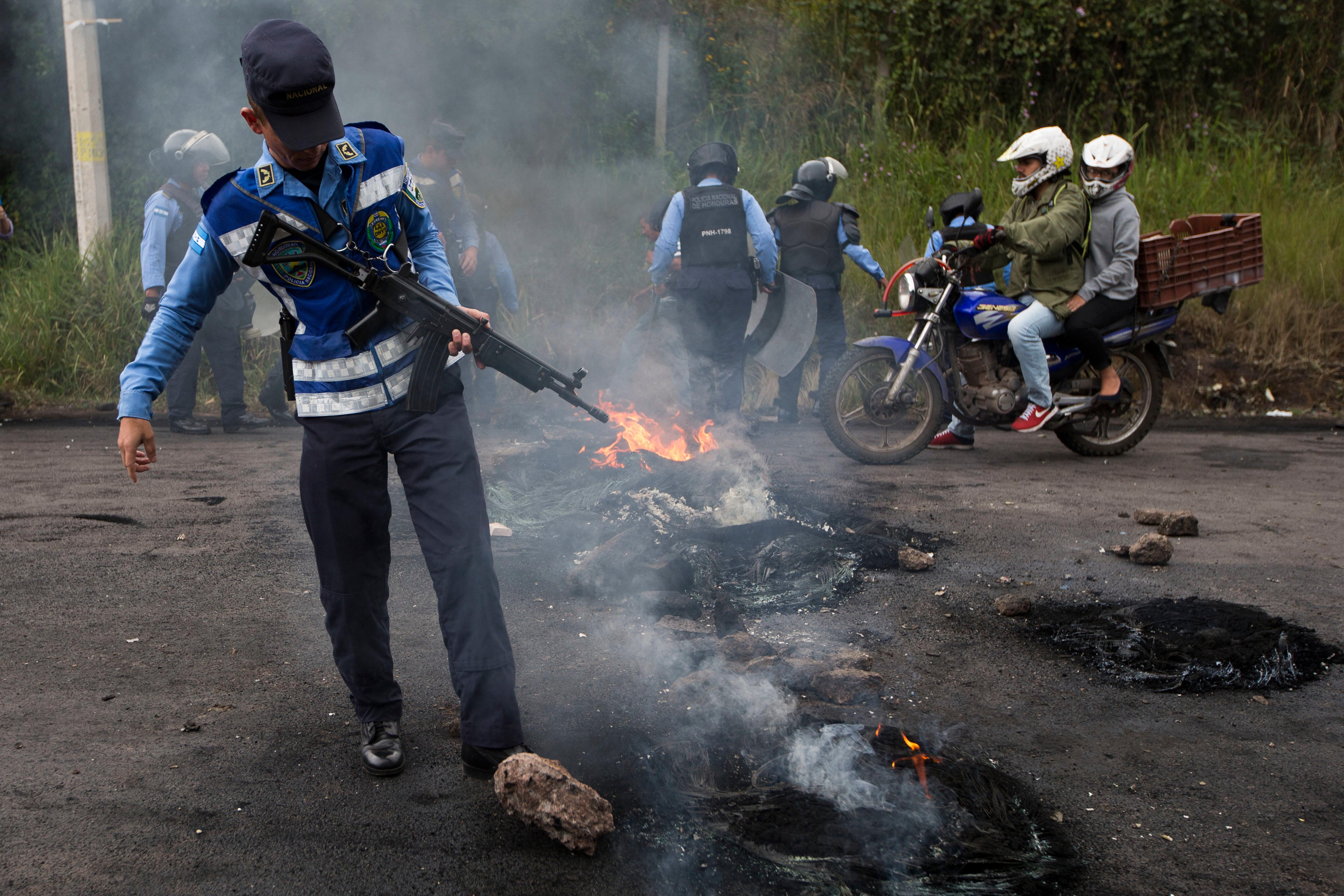 Soldiers clear away a barricade erected by anti-government protestors blocking the road to Valle de los Angeles, on the outskirts of Tegucigalpa, Honduras, Thursday, Dec. 7, 2017. The government has lifted the curfew it imposed last week for nine of the country's 18 provinces, but left it in place for the two biggest cities, Tegucigalpa and San Pedro Sula, armed forces spokesman Jorge Cerrato said. (AP Photo/Moises Castillo)