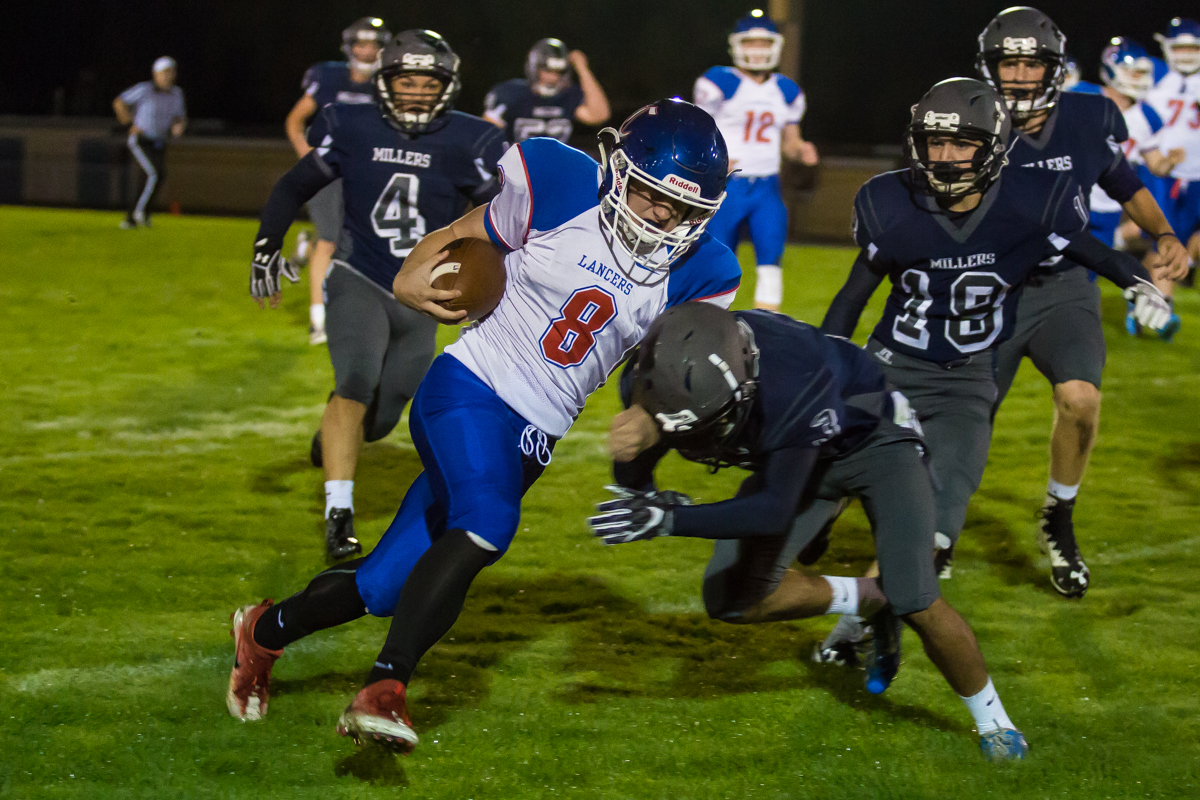 Churchill running back Dalton McDaniel (#8) takes a hit from Springfield cornerback James Difranco (#3). The Churchill Lancers defeated the Springfield Millers 56-7 in a cold game Friday night. Friday night's win extended Churchill's season record to 7-0. Photo by Dillon Vibes
