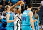 Milwaukee Bucks forward John Henson, second from left, tries to pass around the Charlotte Hornets defense during the first half , Wednesday, Nov. 1, 2017, in Charlotte, N.C.