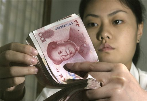 A Chinese bank worker displays Chinese yuan at a bank in Beijing.
