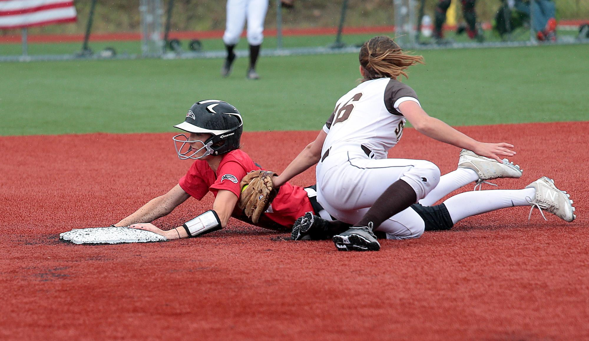 Southern Oregon University freshman Hannah Shimek slides in under the tag by St. Francis Infielder Ashley Galason at US Cellular Community Park on Wednesday.[PHOTO BY:  LARRY STAUTH JR]