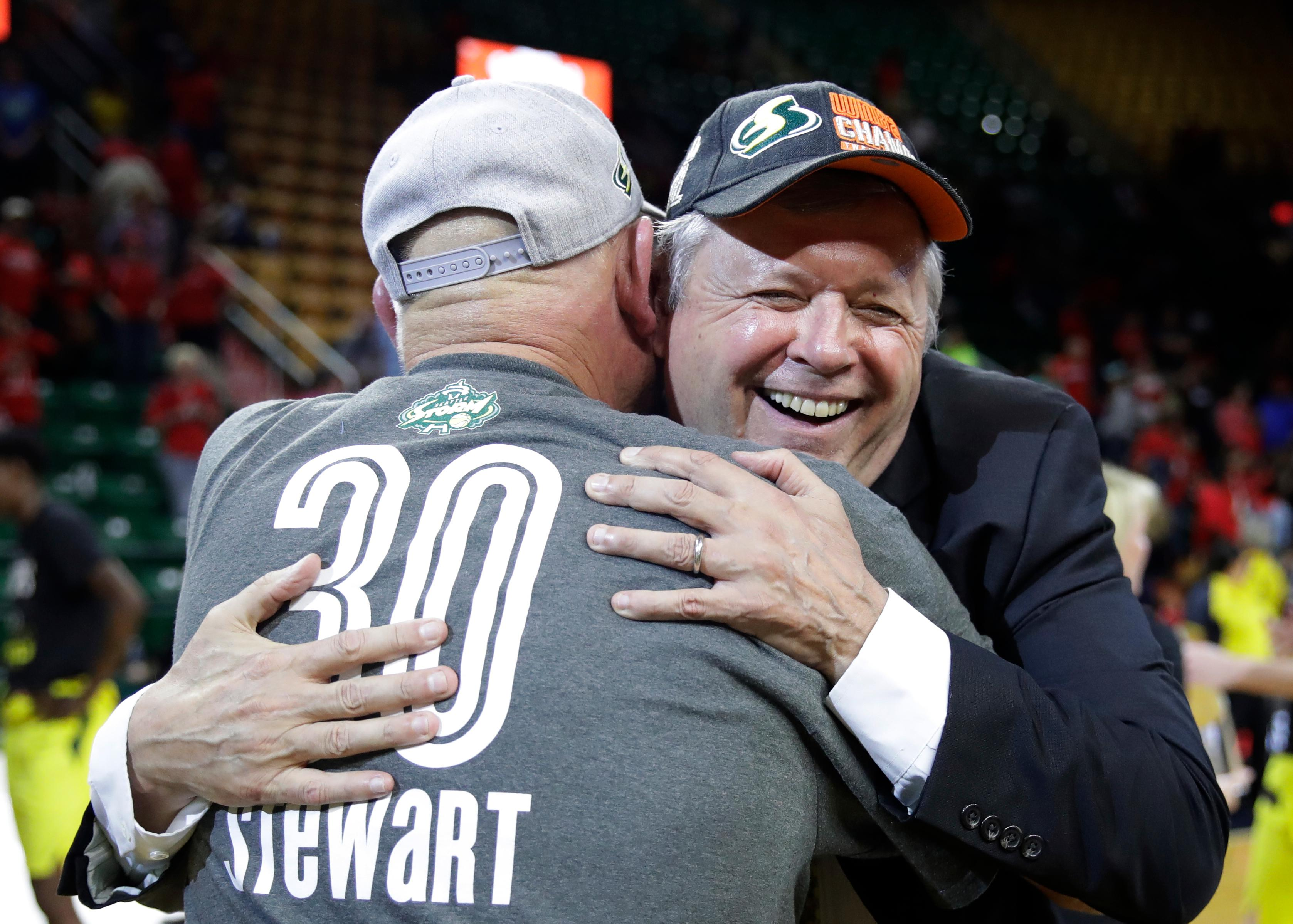 Seattle Storm head coach Dan Hughes hugs a fan on the court after winning Game 3 of the WNBA basketball finals, Wednesday, Sept. 18 2018, in Fairfax, Va. The Seattle Storm defeated the Washington Mystics 98-82. (AP Photo/Carolyn Kaster)